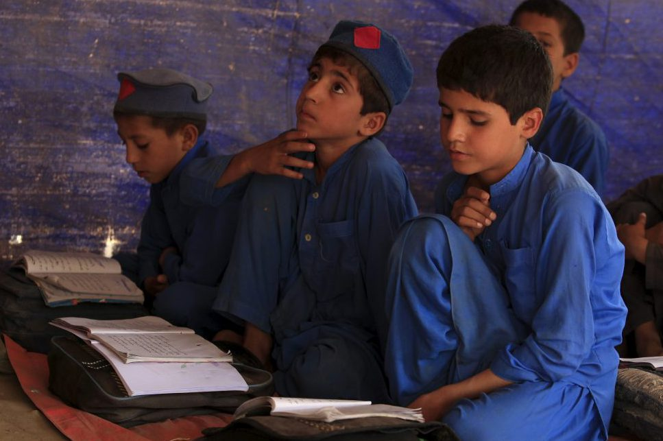 Boys attend a class at a school in Kababiyan refugee camp in Peshawar, Pakistan, October 6, 2015. Aid programmes for some of the 2.5 million Afghan refugees in Pakistan are being slashed amid the worst funding shortfall for a generation, as the European and Syrian migrant crisis uses up cash and dominates headlines, United Nations officials said. Picture taken October 6, 2015. REUTERS/Faisal Mahmood  - RTS49O7
