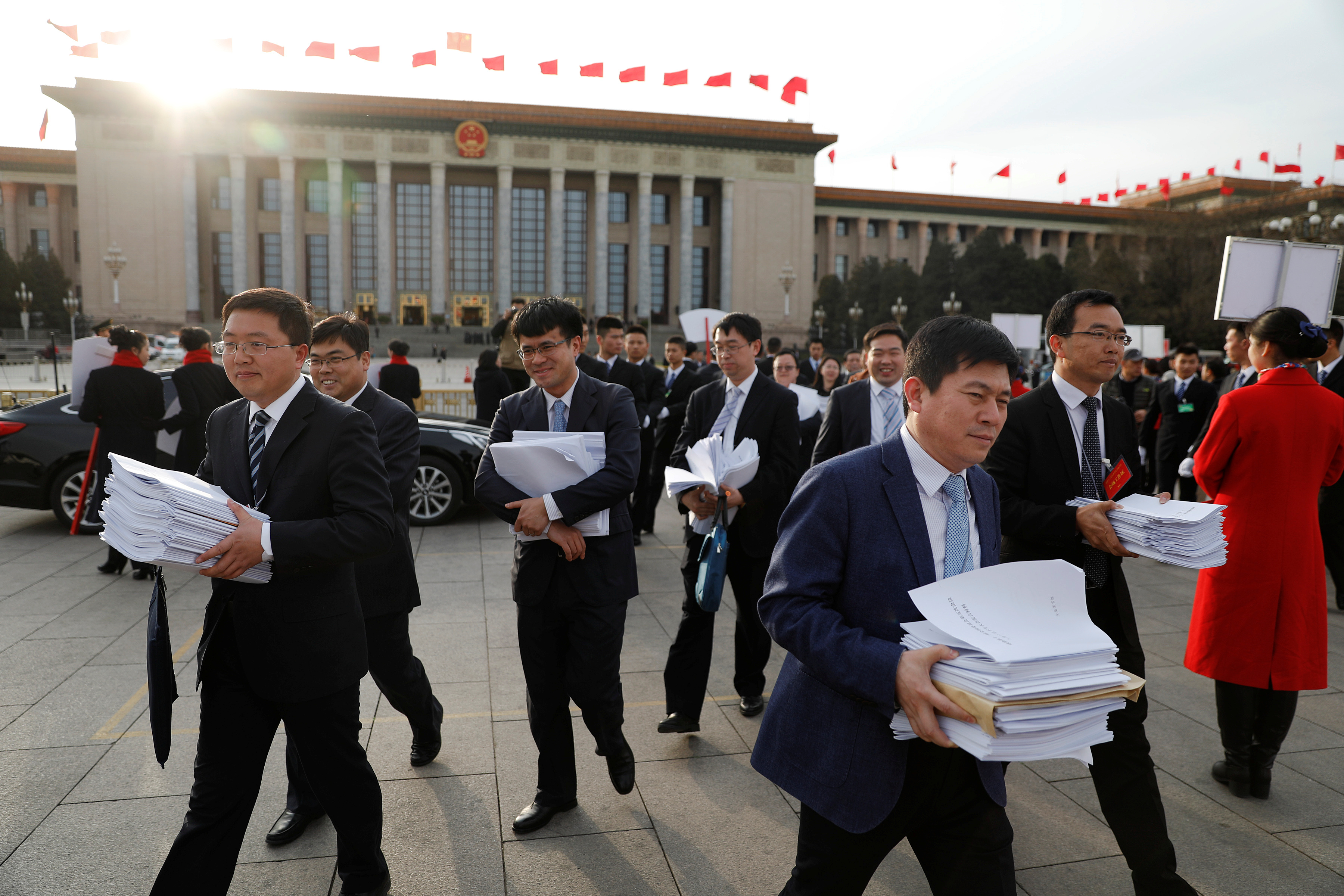 People carry stacks of papers near the Great Hall of the People after a plenary session of the Chinese People's Political Consultative Conference (CPPCC) in Beijing, China, March 11, 2017. REUTERS/Damir Sagolj - RTX30K0G