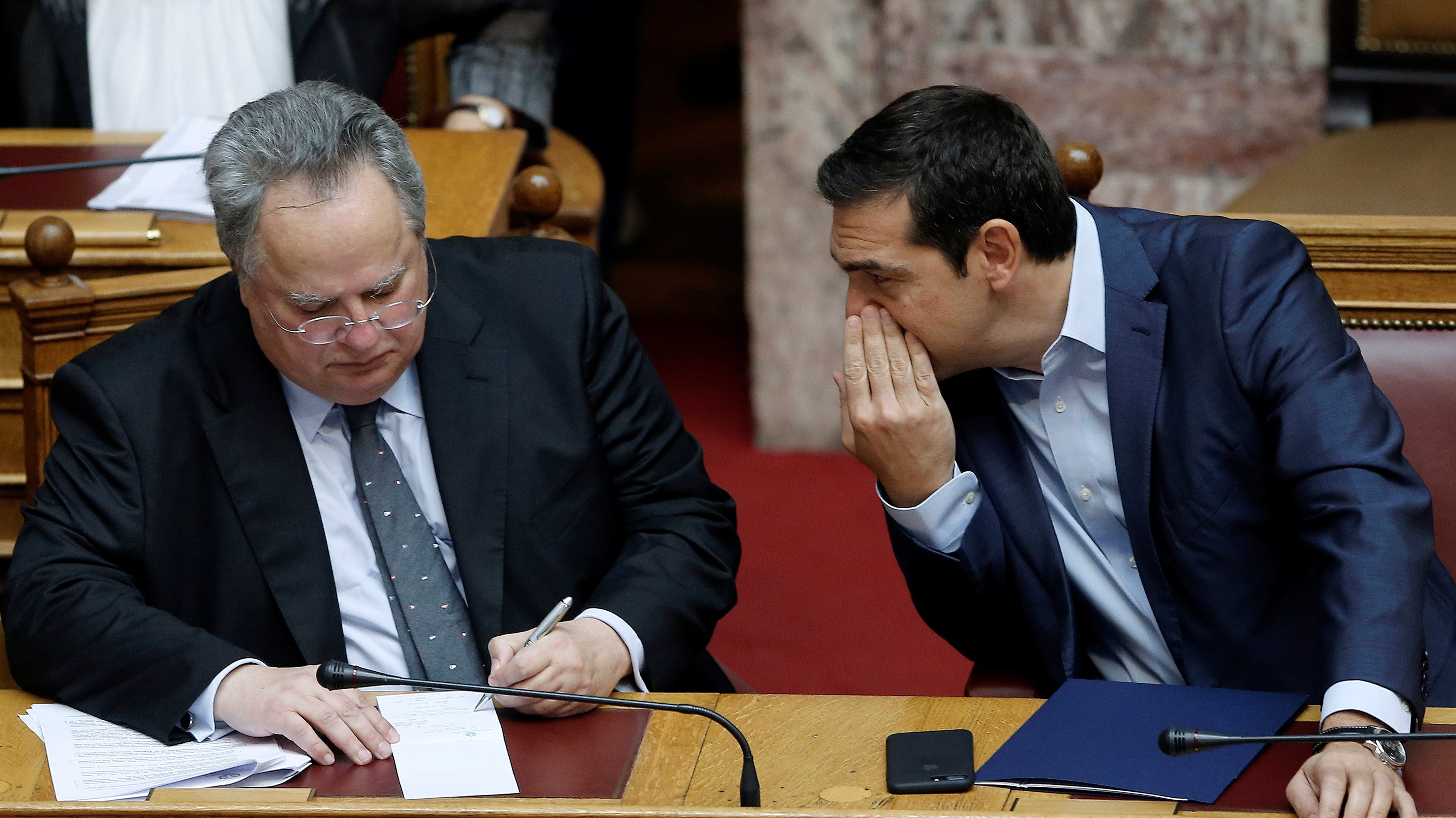 Greek Prime Minister Alexis Tsipras (R) talks with Greek Foreign Minister Nikos Kotzias during a parliamentary session on the collapse of Cyprus peace talks in Athens, Greece July 11, 2017. REUTERS/Costas Baltas - RTX3AZPO