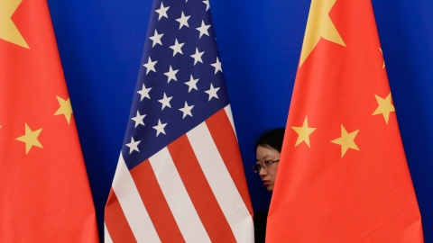 A member of staff from Chinese government adjusts U.S. and Chinese national flags before a news conference for the 6th round of U.S.-China Strategic and Economic Dialogue at the Great Hall of the People in Beijing, July 10, 2014. REUTERS/Jason Lee (CHINA - Tags: POLITICS BUSINESS) - RTR3XZ0B