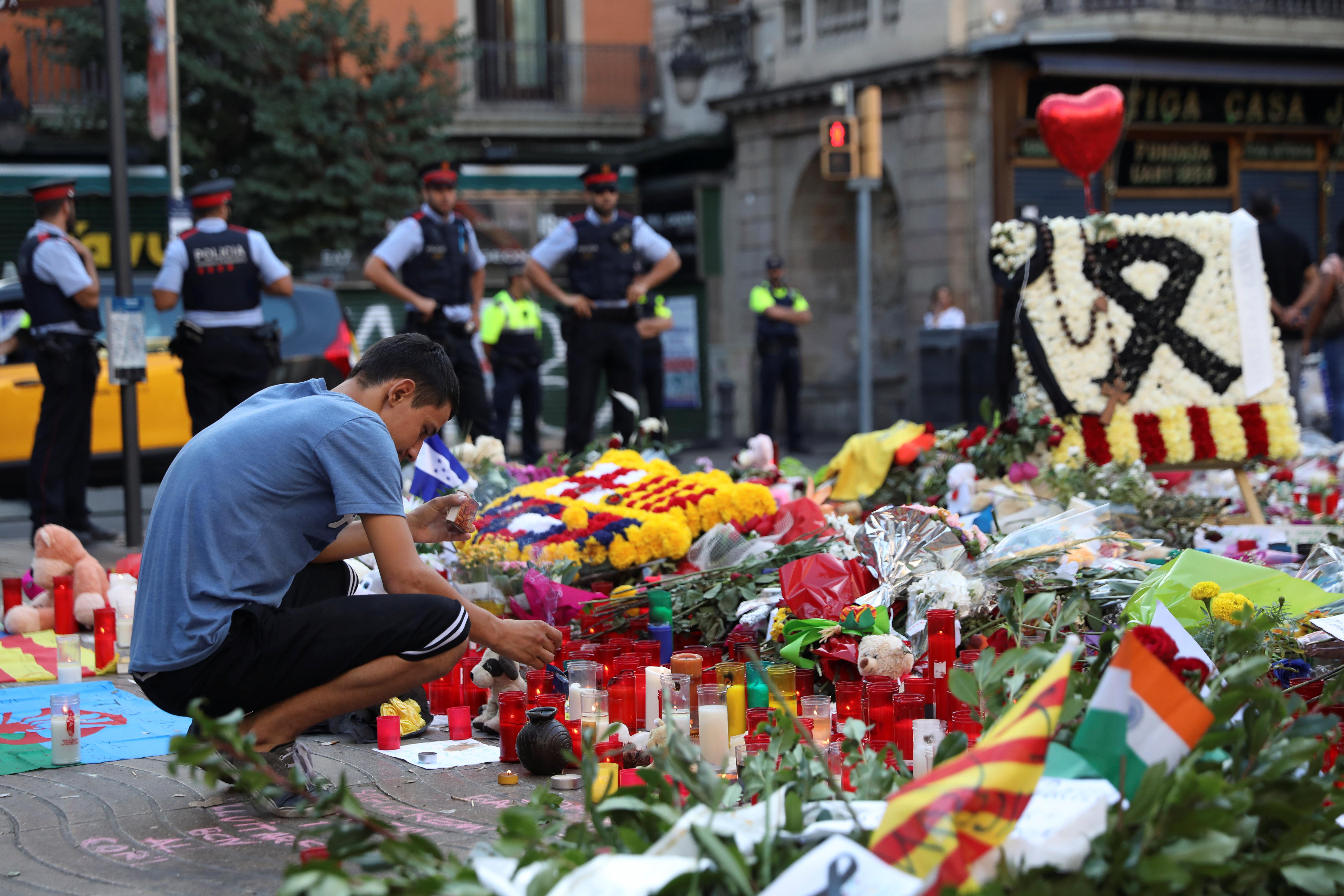 A man lights a candle at an impromptu memorial where a van crashed into pedestrians at Las Ramblas in Barcelona, Spain August 21, 2017. REUTERS/Susana Vera - RTS1CLTL