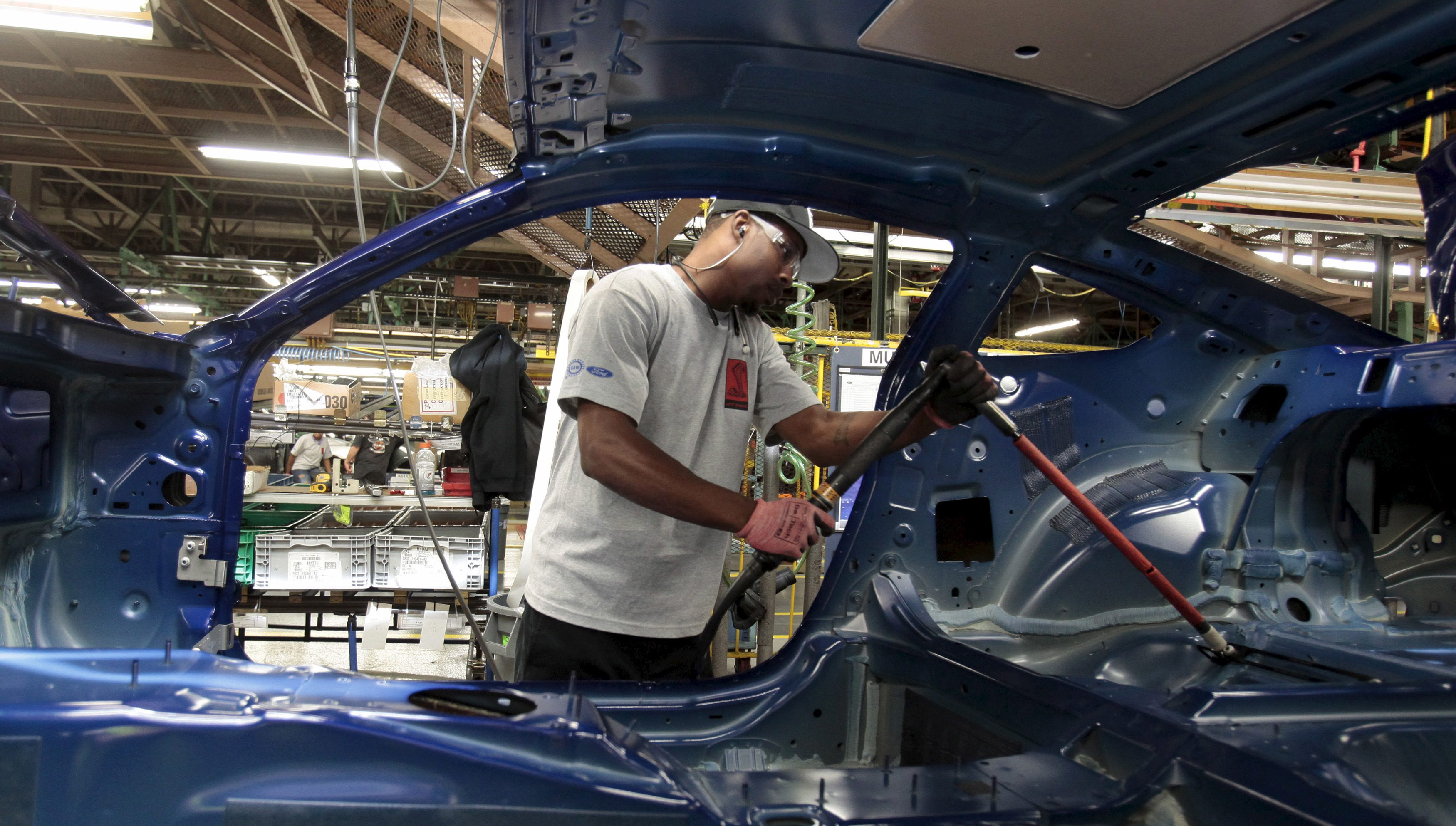 A Ford Motor assembly worker works on the frame of a 2015 Ford Mustang vehicle at the Ford Motor Flat Rock Assembly Plant in Flat Rock, Michigan, August 20, 2015. REUTERS/Rebecca Cook - RTX1OYPW