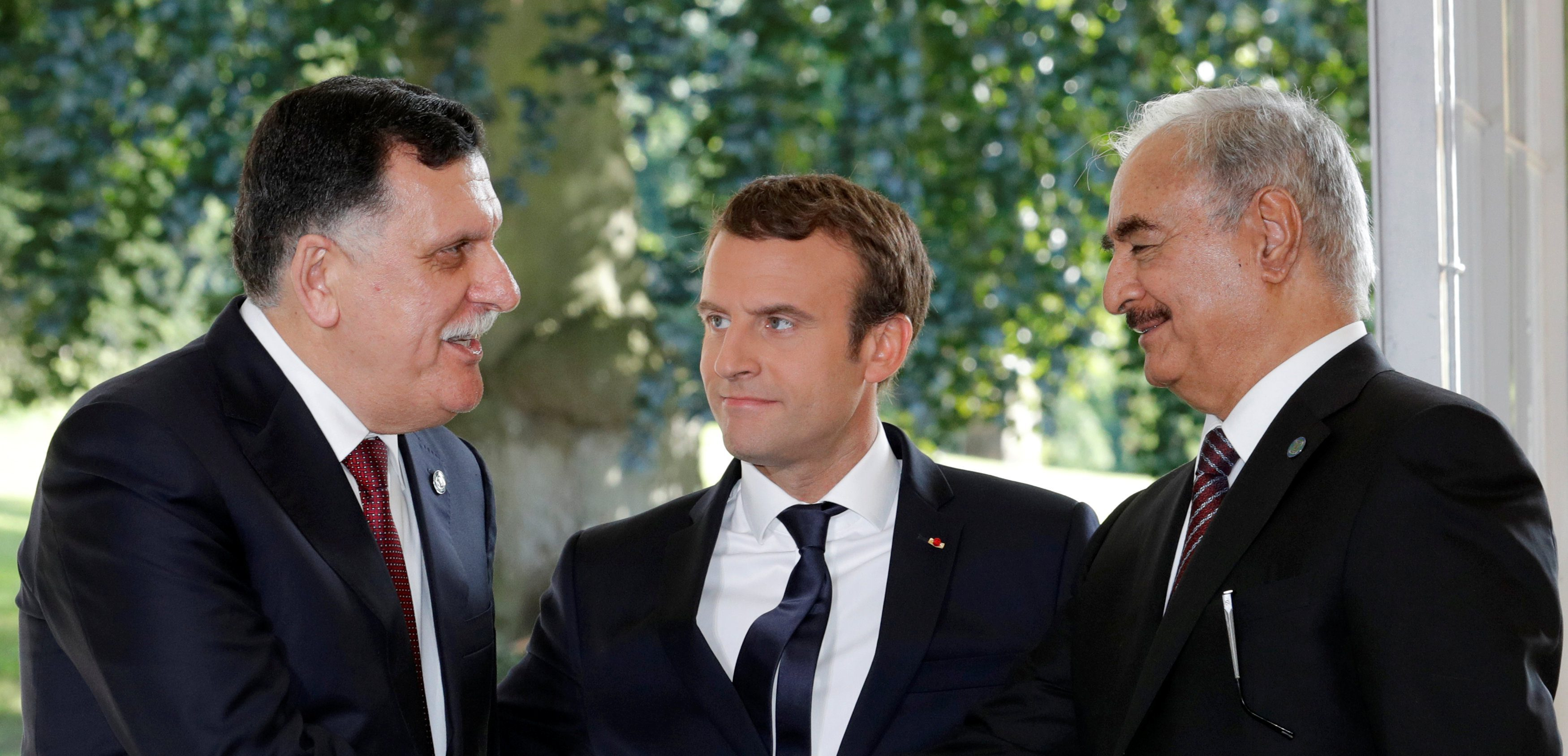 French President Emmanuel Macron stands between Libyan Prime Minister Fayez al-Sarraj (L), and General Khalifa Haftar (R), commander in the Libyan National Army (LNA), who shake hands after talks over a political deal to help end Libya's crisis in La Celle-Saint-Cloud near Paris, France, July 25, 2017. REUTERS/Philippe Wojazer TPX IMAGES OF THE DAY - RTX3CVLX