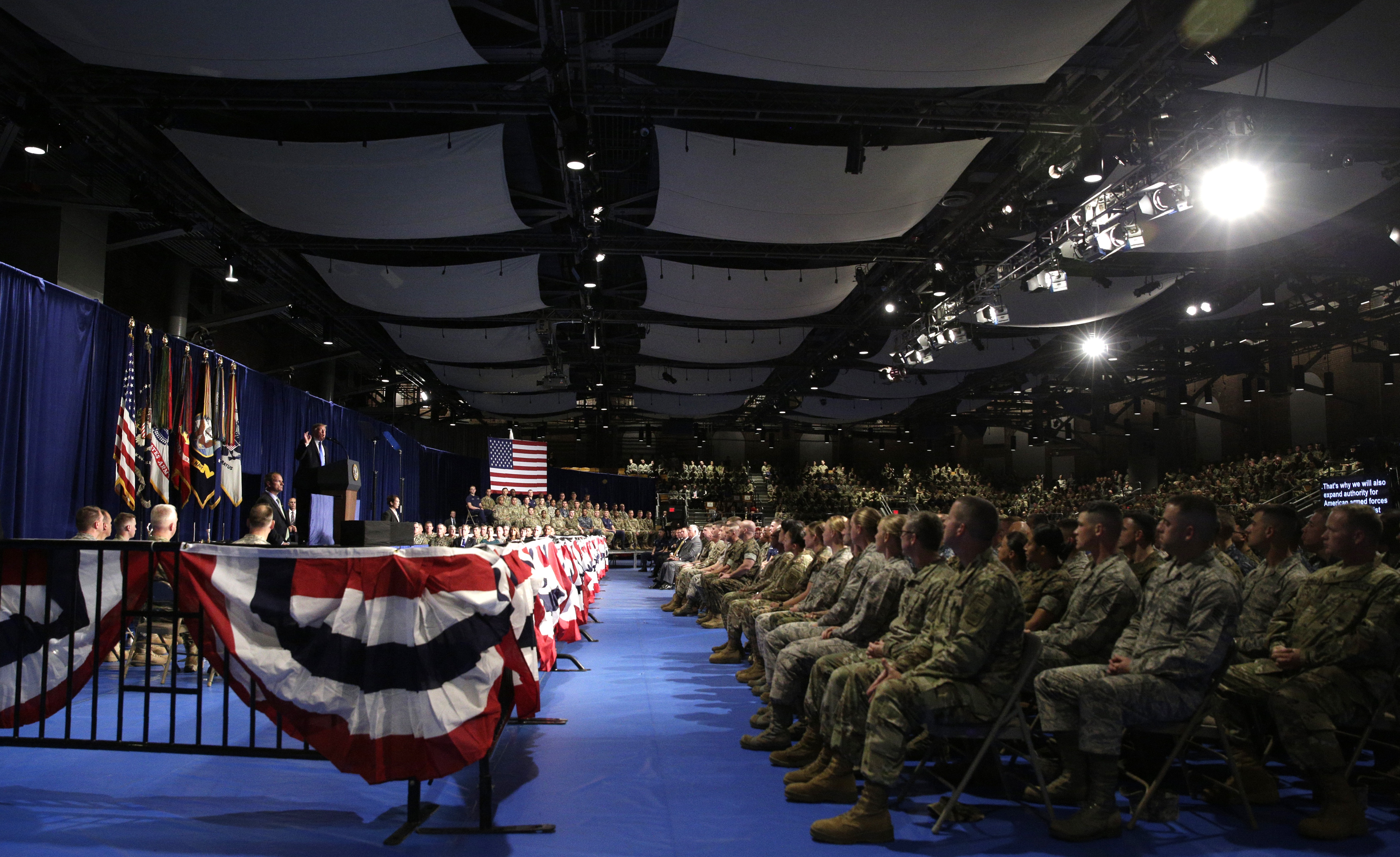 Military personnel watch as U.S. President Donald Trump (L) announces his strategy for the war in Afghanistan during an address to the nation from Fort Myer, Virginia, U.S., August 21, 2017. REUTERS/Joshua Roberts - RTS1CQS1