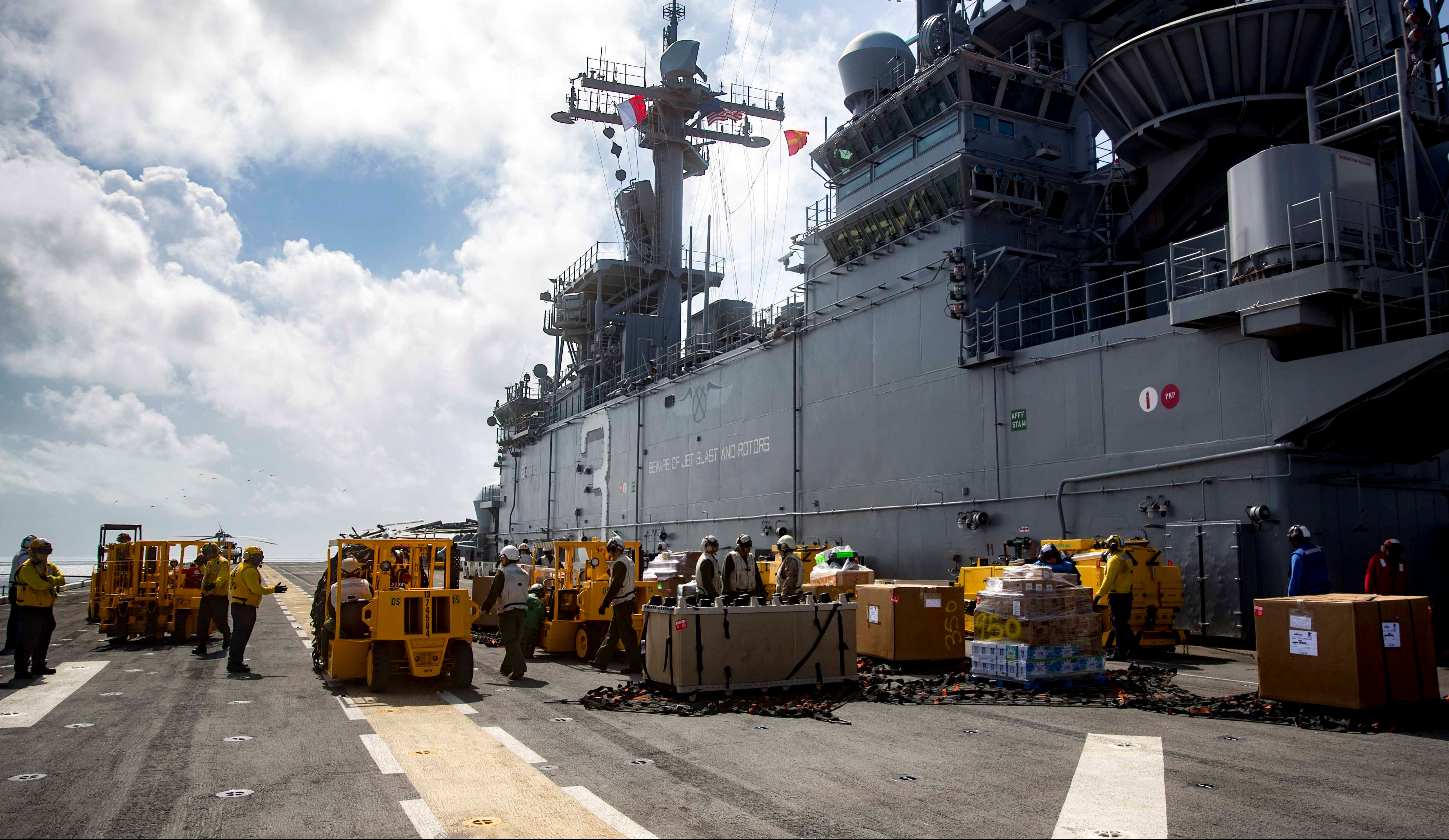 Sailors aboard the amphibious assault ship USS Kearsarge (LHD 3) move pallets of supplies on the flight deck during a replenishment-at-sea with the fast combat support ship USNS Supply (T-AOE 6) for relief efforts in the aftermath of Hurricane Maria in Puerto Rico on September 28, 2017. Picture taken on September 28, 2017. Courtesy Ryre Arciaga/U.S. Navy/Handout via REUTERS ATTENTION EDITORS - THIS IMAGE HAS BEEN SUPPLIED BY A THIRD PARTY. - RC1F885AD890