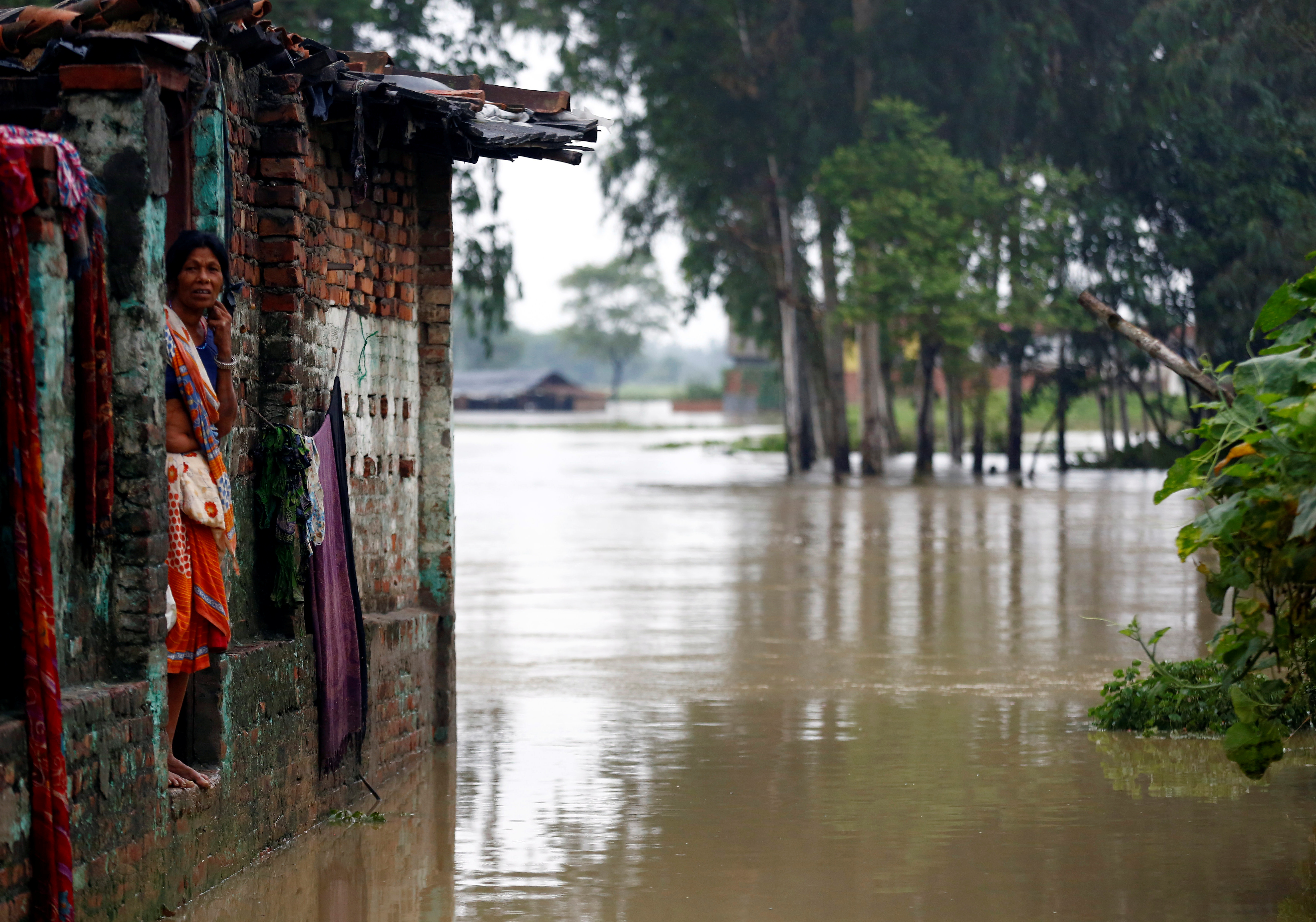 A woman looks out from her house at a flood affected area in Nepal