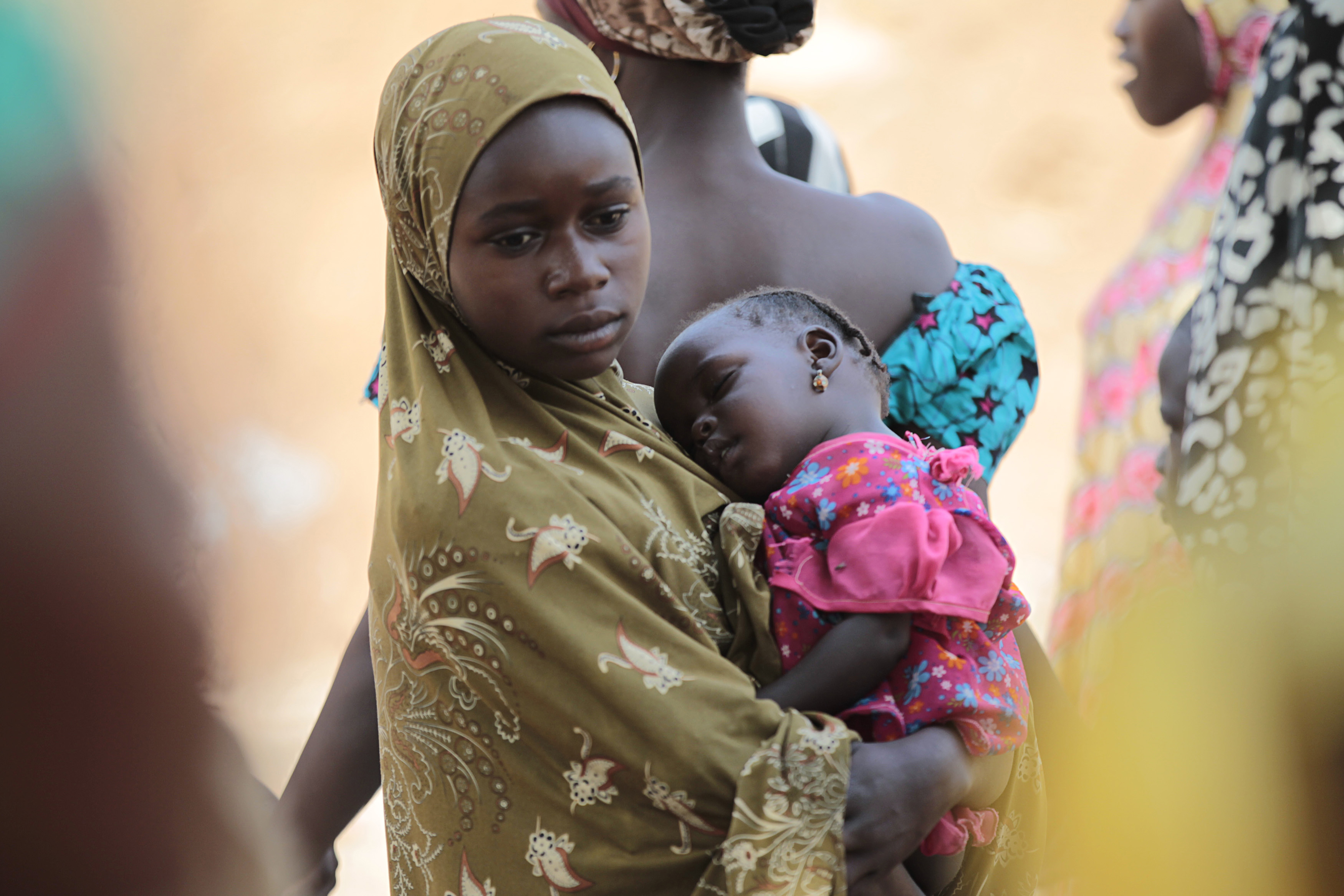 A girl carries a sleeping baby at a camp for displaced people fleeing violence from Gulak, a border town in the north of Adamawa state which was attacked in September 2014, January 31, 2015. REUTERS/Afolabi Sotunde (NIGERIA - Tags: CIVIL UNREST POLITICS) - GM1EB210WIL01