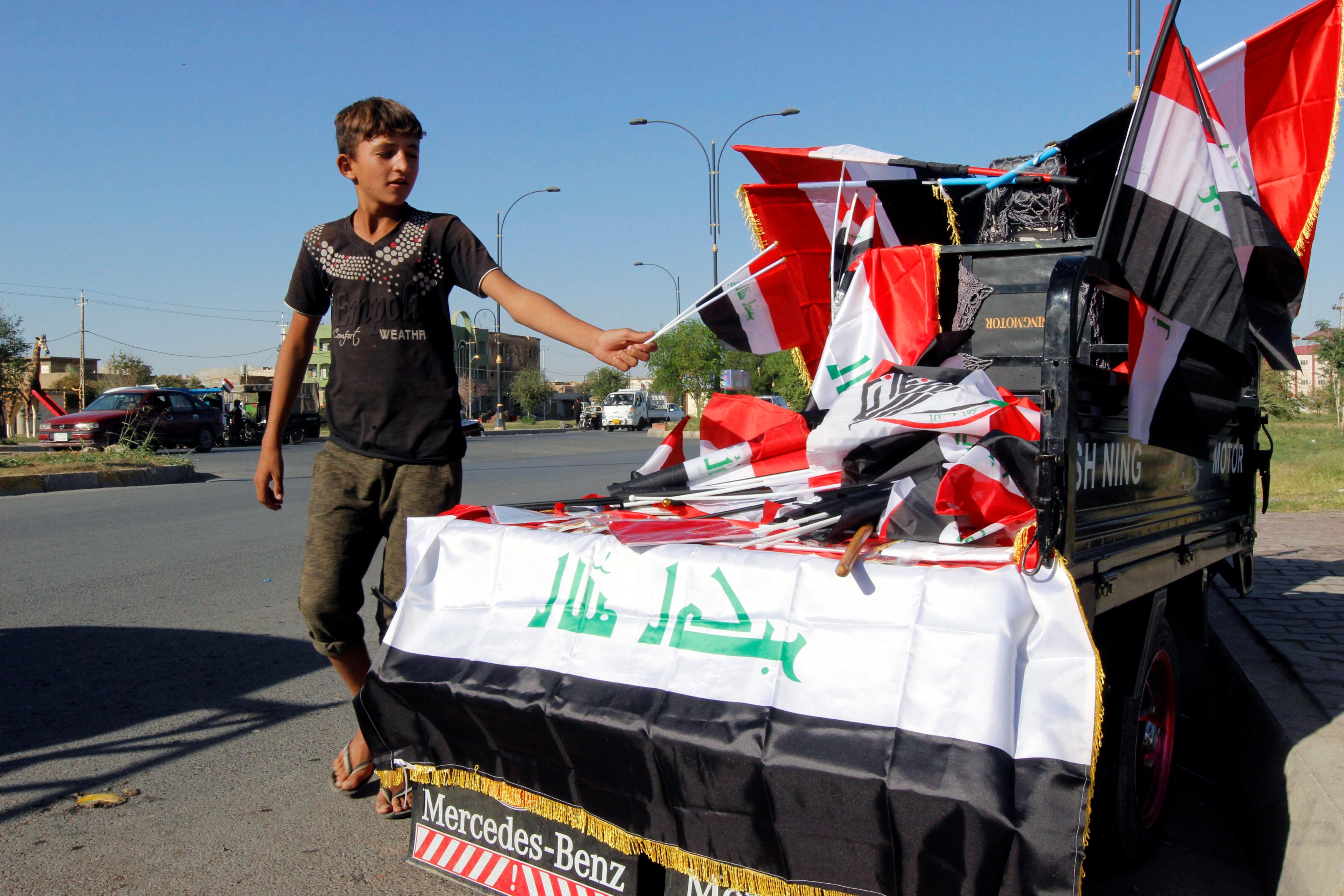 A boy sells Iraqi flags on a street in Kirkuk, Iraq October 19, 2017. REUTERS/Ako Rasheed - RC13D638D300