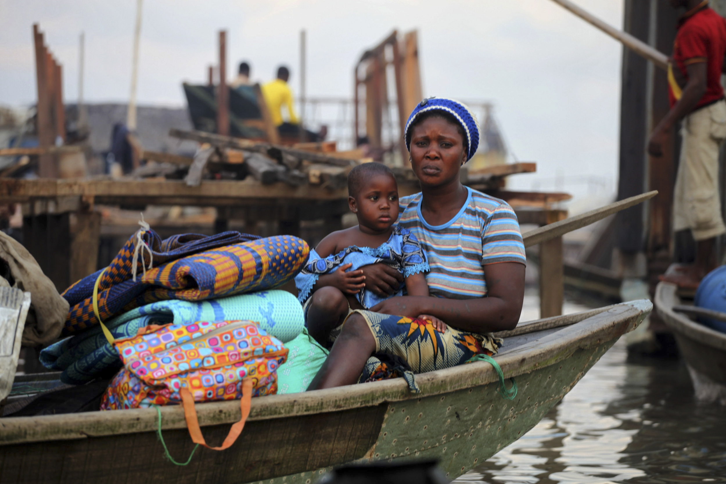 A woman sits in a canoe with her belongings as the metropolitan government begins the demolition of structures in the Makoko riverine community in Lagos July 16, 2012. The structures were deemed illegal as they were built without permission on Lagos Lagoon. REUTERS/Akintunde Akinleye  (NIGERIA - Tags: POLITICS SOCIETY POVERTY) - GM1E87H0HZK01