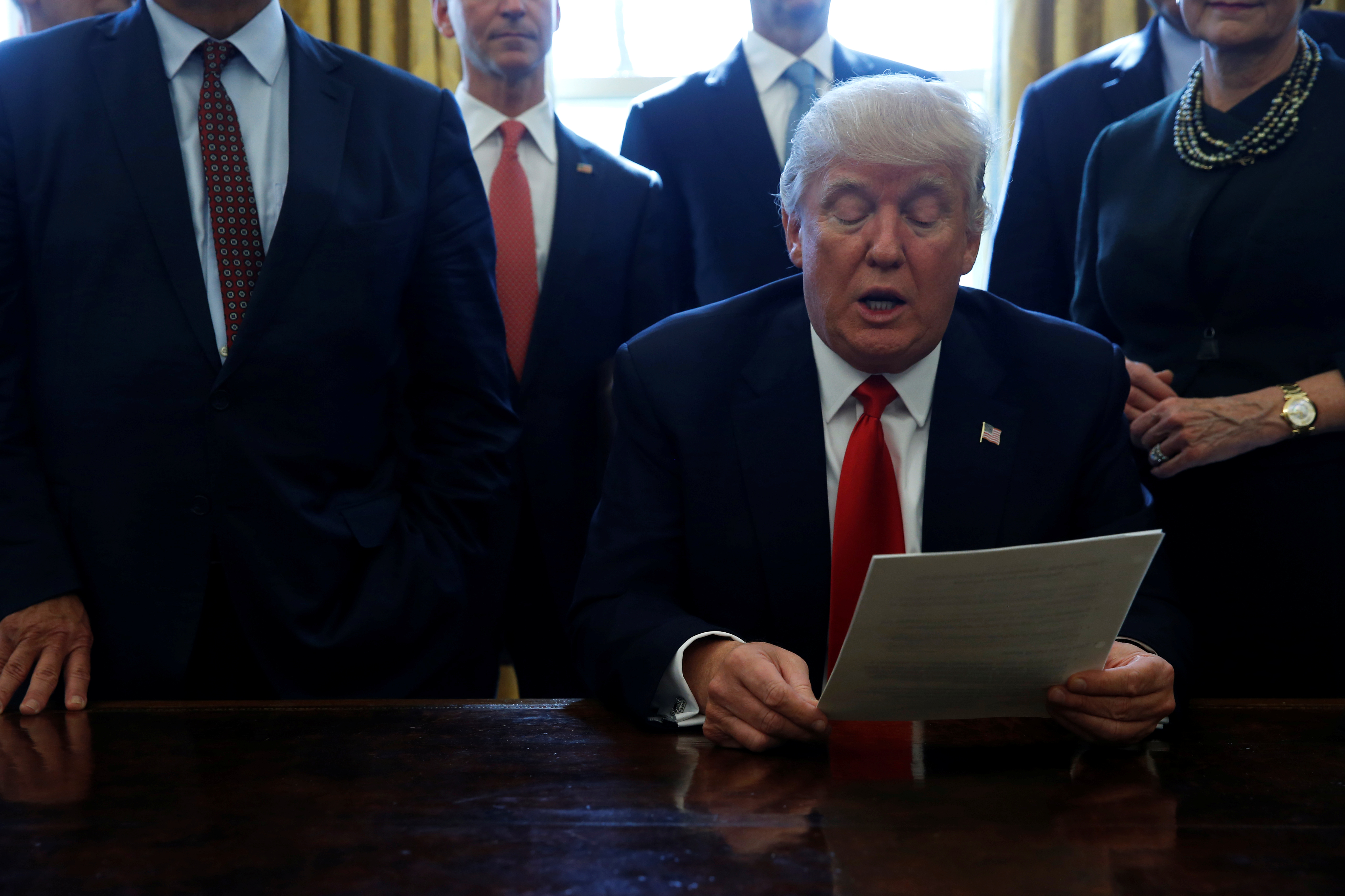 U.S. President Donald Trump is surrounded by business leaders as he delivers remarks before signing an executive order on regulatory reform at his desk in the Oval Office at the White House, U.S. February 24, 2017. REUTERS/Jonathan Ernst - RC1B6DF7B3F0