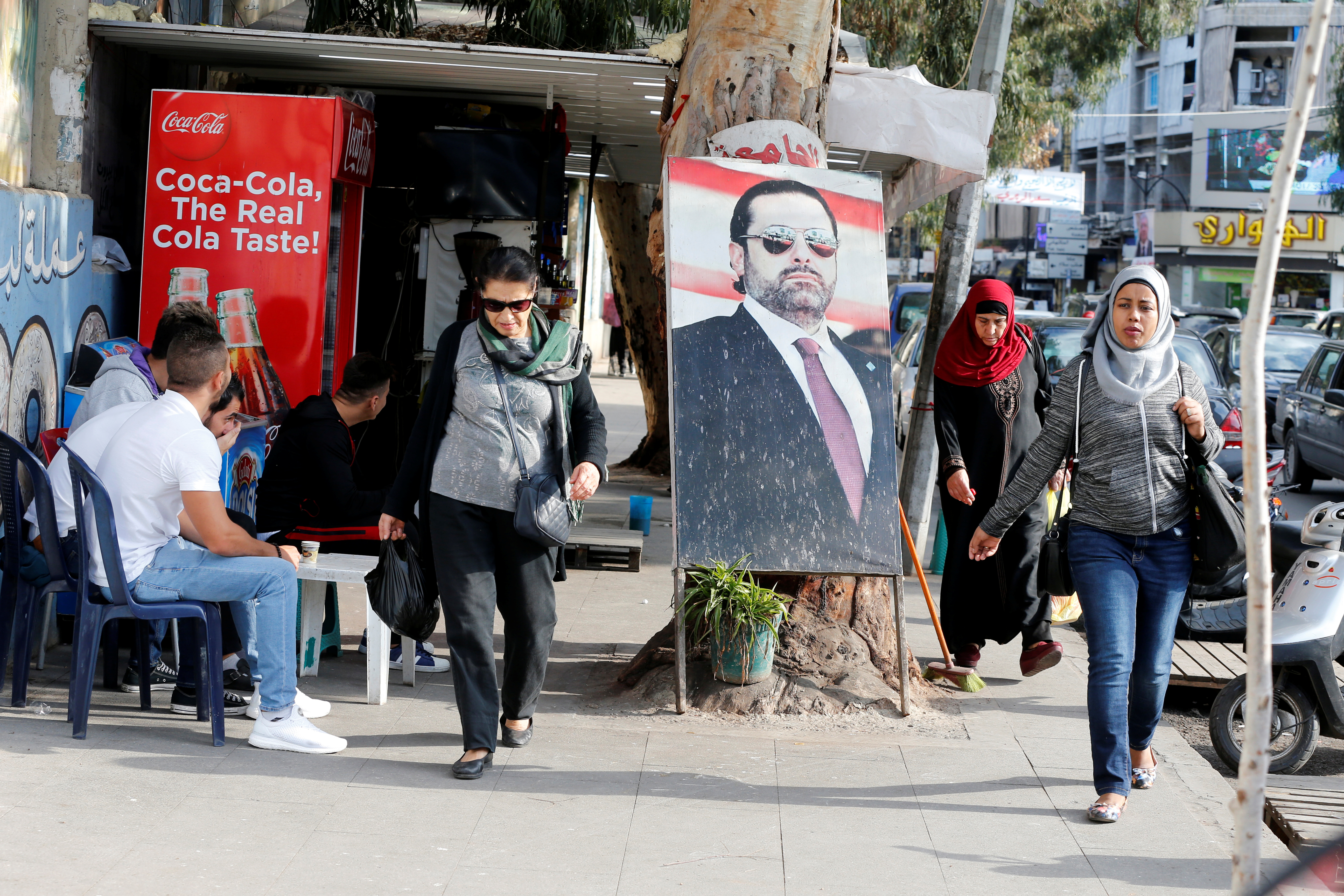 People walk next to a poster depicting Lebanon's Prime Minister Saad al-Hariri, who has resigned from his post, along a street in the mainly Sunni Beirut neighbourhood of Tariq al-Jadideh in Beirut, Lebanon November 6, 2017. REUTERS/Mohamed Azakir - RC1556EE7010