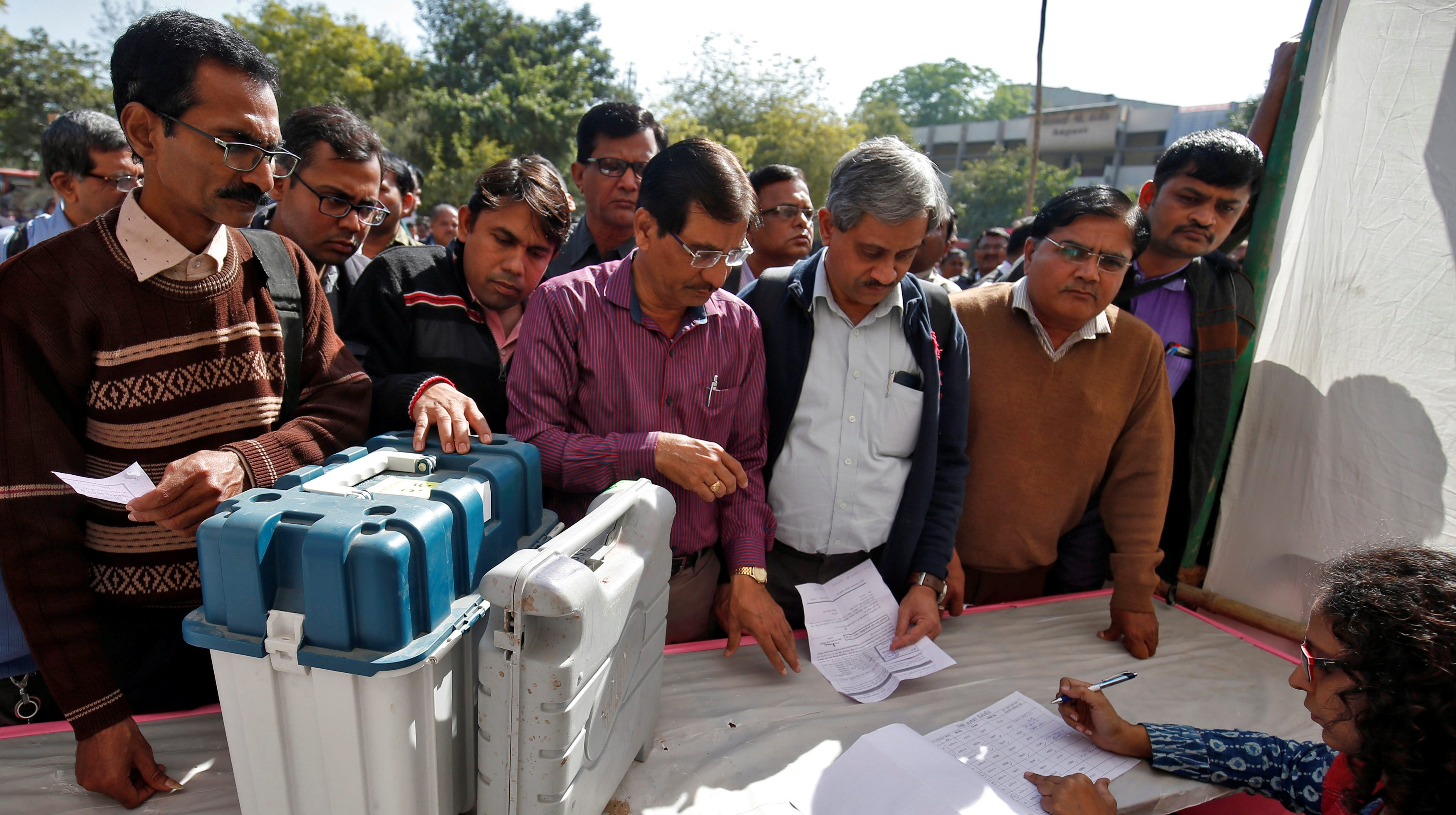 Polling officials wait to receive Voter Verifiable Paper Audit Trail (VVPAT) machines and Electronic Voting Machines (EVM) at a distribution centre ahead of the final phase of voting in Gujarat state assembly election in Ahmedabad, India, December 13, 2017. REUTERS/Amit Dave - RC1F07DFD550