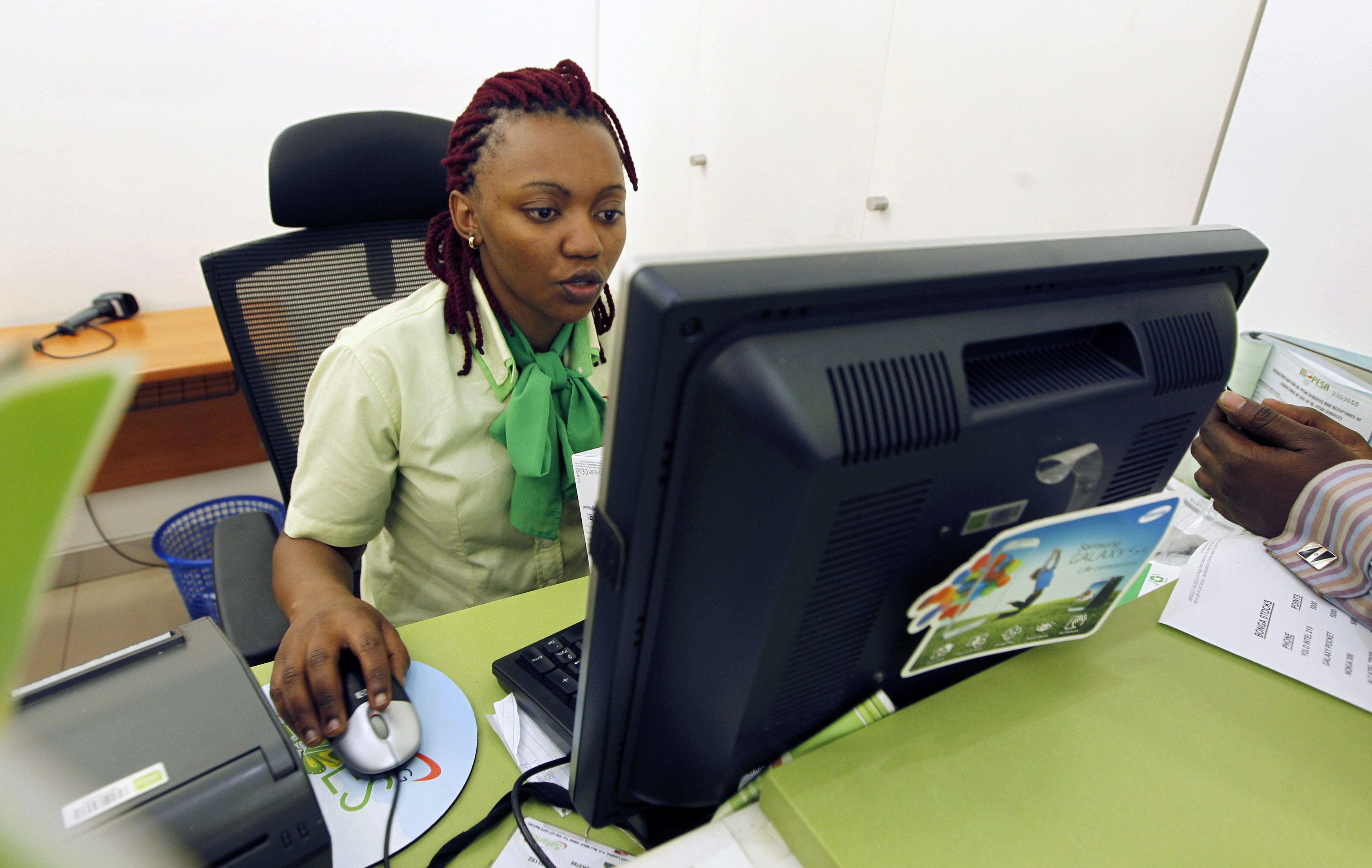 An employee registers a customer for a mobile money transfer, known as M-Pesa, inside the Safaricom mobile phone care centre in the central business district of Kenya's capital Nairobi July 15, 2013. To match Insight AFRICA-MOBILEMONEY/   Picture taken July 15, 2013.  REUTERS/Thomas Mukoya (KENYA - Tags: BUSINESS TELECOMS) - GM1EA7U1QTU01