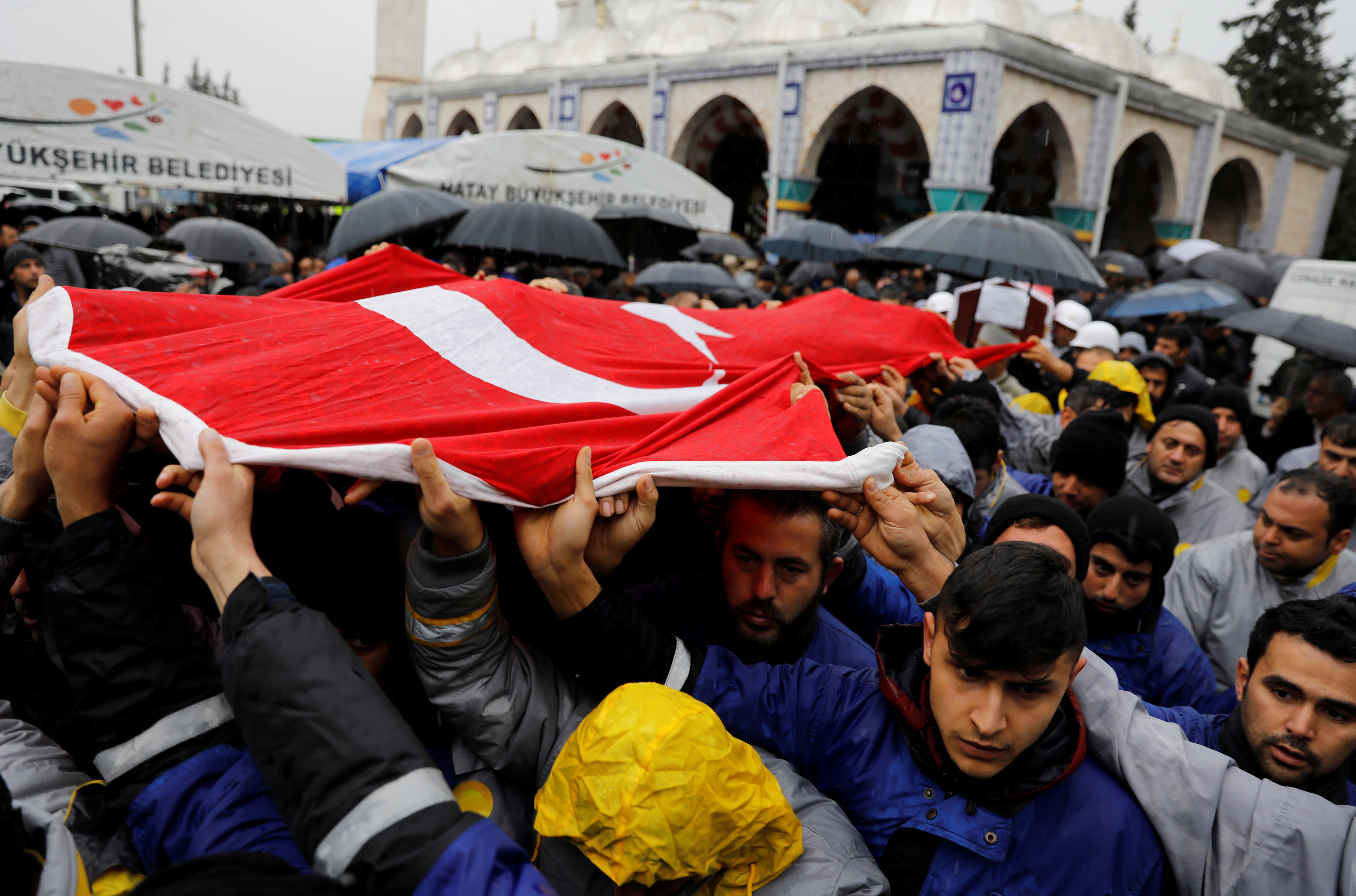 Relatives and friends of Sahin Elitas, a civilian who was killed in a rocket attack fired by Syria, carry a Turkish flag during his funeral ceremony in the town of Kirikhan in Hatay province, Turkey January 23, 2018.