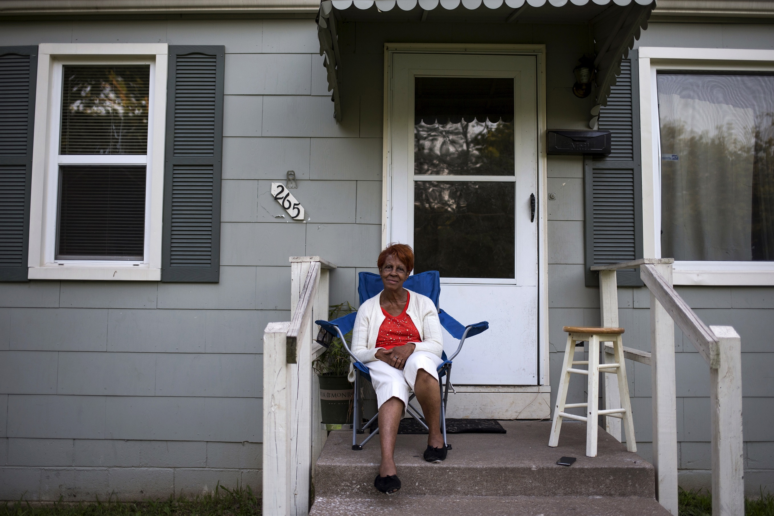 """Cora Gates, 68, a grandmother, poses for a portrait outside her family home in Ferguson, Missouri July 23, 2015. When asked how Michael Brown's death affected her life, Gates said, """"It didn't affect my life at all. I still sit on the porch like normal. I heard the guns but I didn't do nothing so I don't have to be afraid of nobody."""" When asked what changes she has seen in her community over the past year, Gates said, """"I don't get out of the house much so I cannot say."""" On August 9, 2014 a white police officer shot unarmed black teenager Michael Brown dead in the St. Louis suburb of Ferguson, Missouri. A year later Reuters photographer Adrees Latif returned to Ferguson, where he has documented events in the past year, to capture the portraits of local residents and canvass their views. REUTERS/Adrees Latif  PICTURE 5 OF 13 FOR WIDER IMAGE STORY """"PORTRAITS OF FERGUSON""""SEARCH """"LATIF PORTRAITS"""" FOR ALL PICTURES - GF20000014304"""