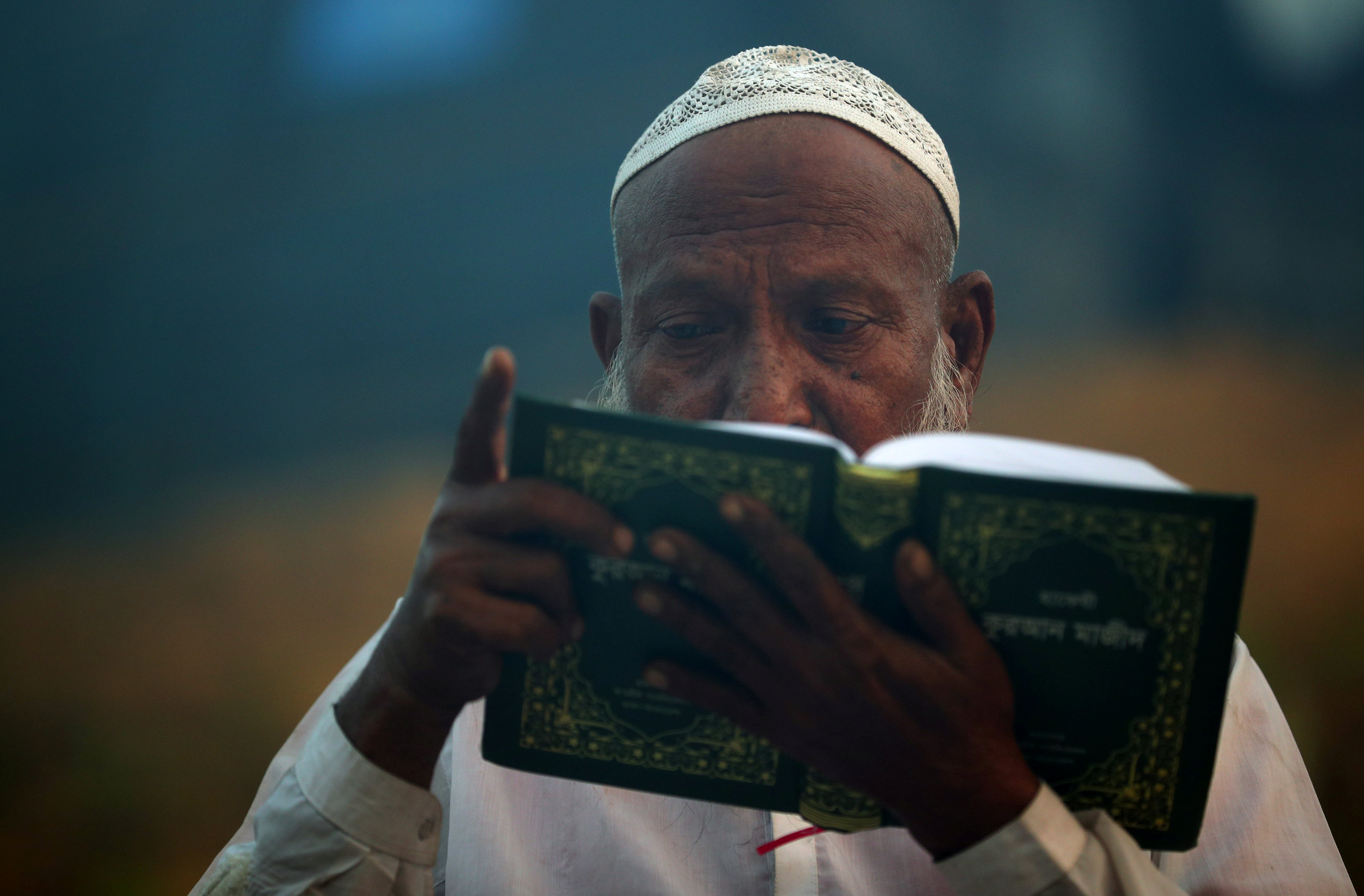 A Rohingya refugee reads the Quran during sunrise in Balukhali refugee camp near Cox's Bazar, Bangladesh, October 26, 2017. REUTERS/Hannah McKay - RC1E91534850