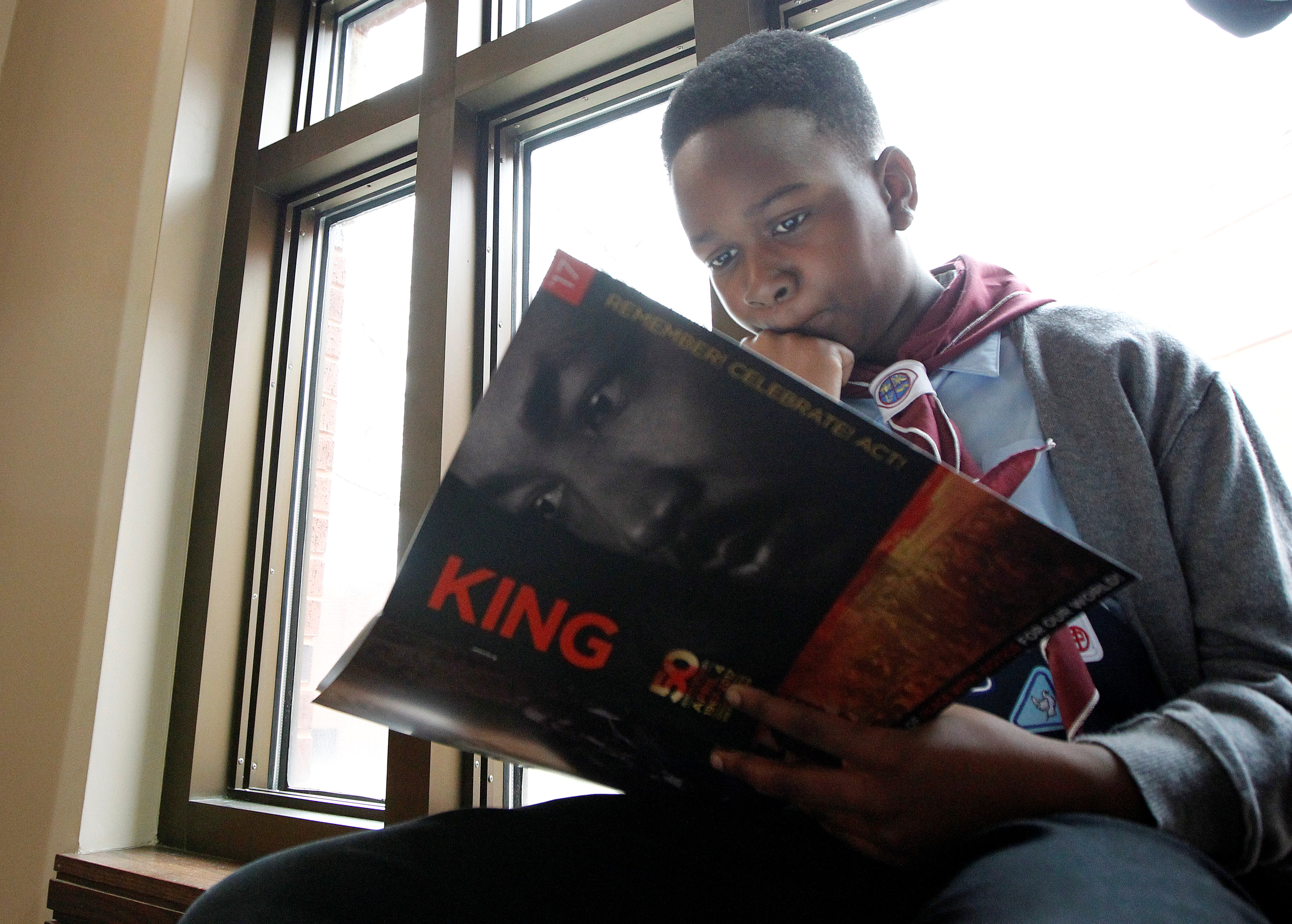 Nine-year old Micah Brown looks over the King program as he sits along a window during the Martin Luther King Jr. Commemorative Service at Ebenezer Baptist Church in Atlanta, Georgia, U.S. January 16, 2017. REUTERS/Tami Chappell - RC1EB13B3AB0