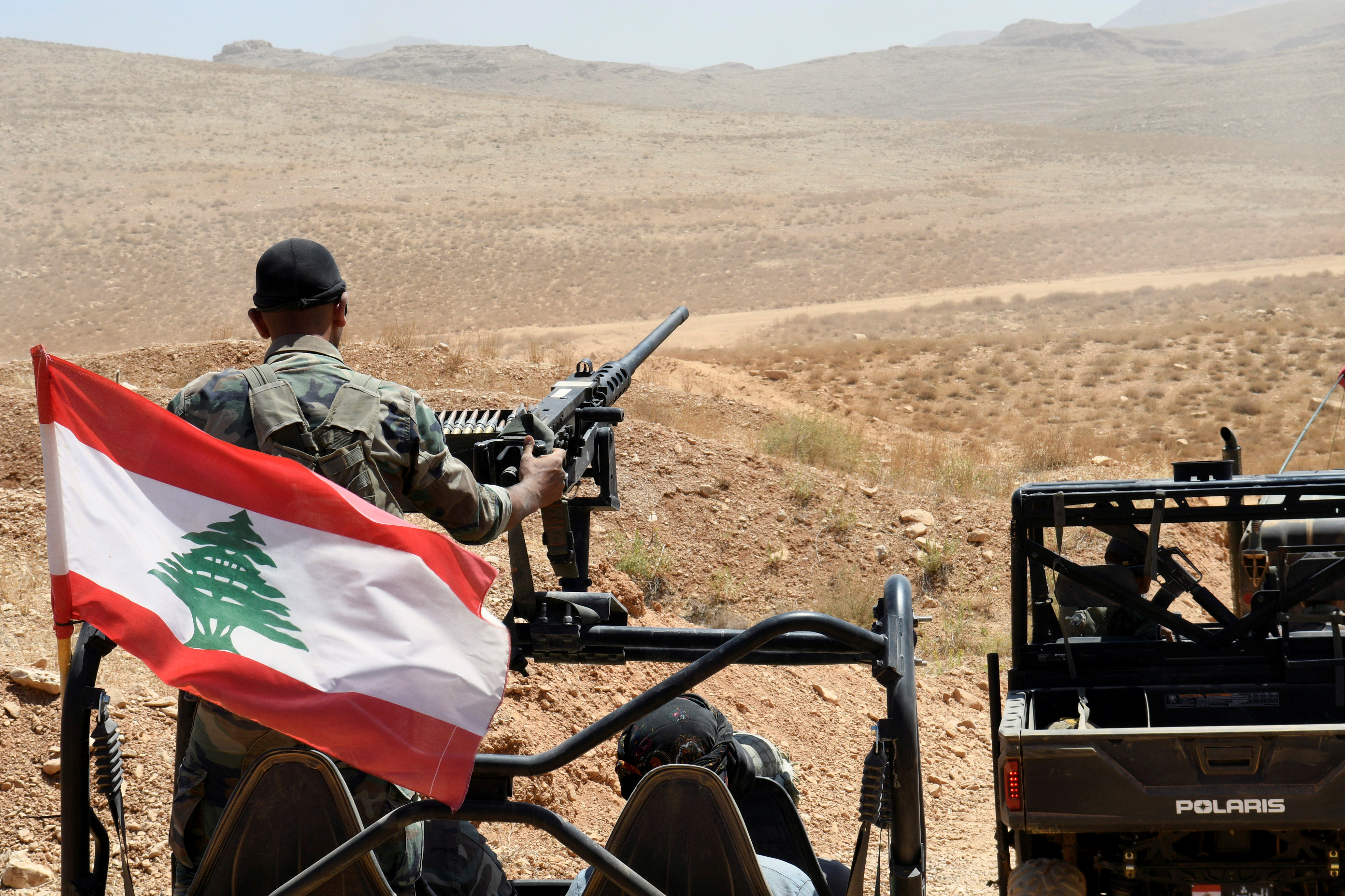 Lebanese Army soldiers ride on their military vehicles in Ras Baalbek