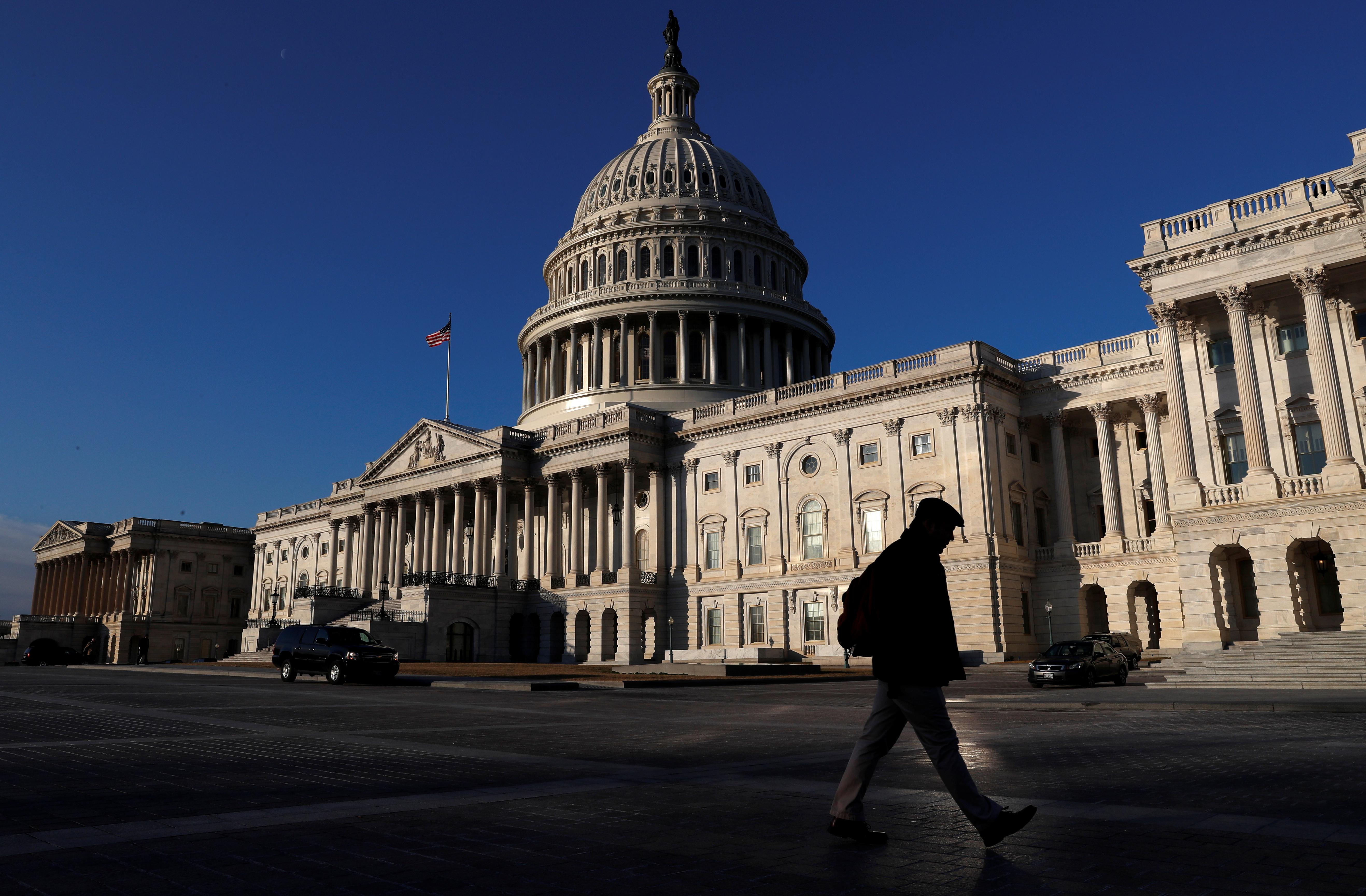 People walk by the U.S. Capitol building in Washington, U.S., February 8, 2018. REUTERS/ Leah Millis - RC13737E70C0