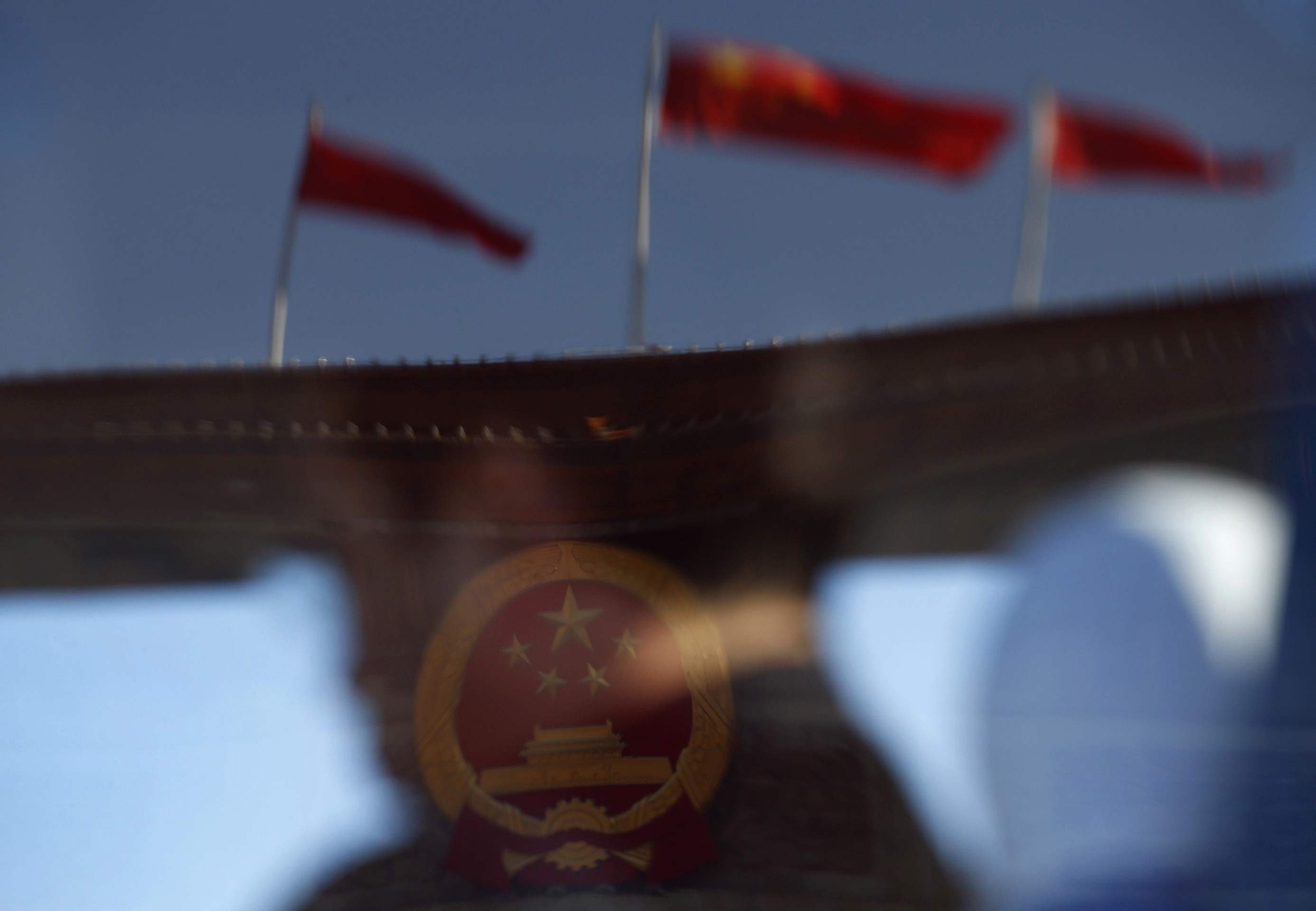 A delegate and the Great Hall of the People, the venue of the 18th National Congress of the Communist Party of China, are reflected in a window of a bus, on Tiananmen Square in Beijing, November 14, 2012.