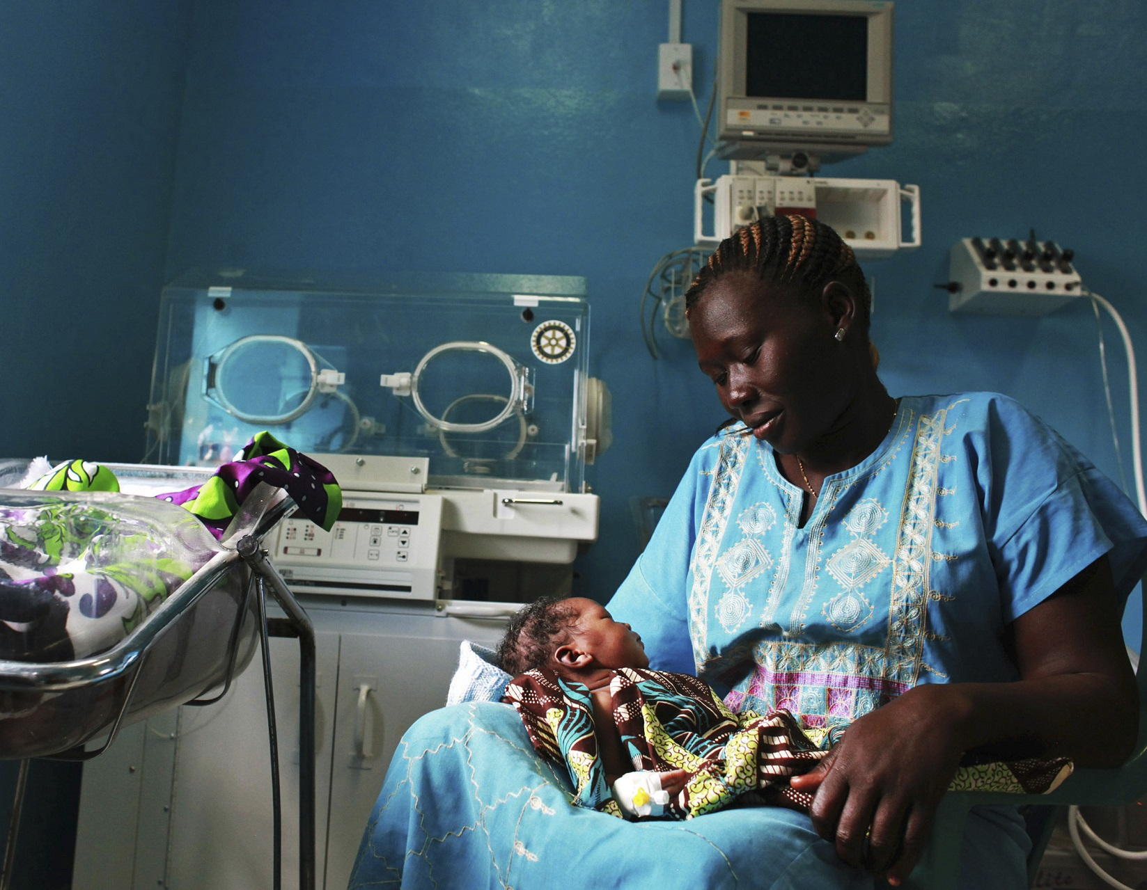 A woman holds her newborn baby in a nursery at the Juba Teaching Hospital in Juba April 3, 2013. Very few births in South Sudan, which has the highest maternal mortality rate in the world at 2,054 per 100,000 live births, are assisted by trained midwives, according to the UNDP's website. Picture taken April 3, 2013. REUTERS/Andreea Campeanu (SOUTH SUDAN - Tags: SOCIETY HEALTH) - GM1E94416HS01