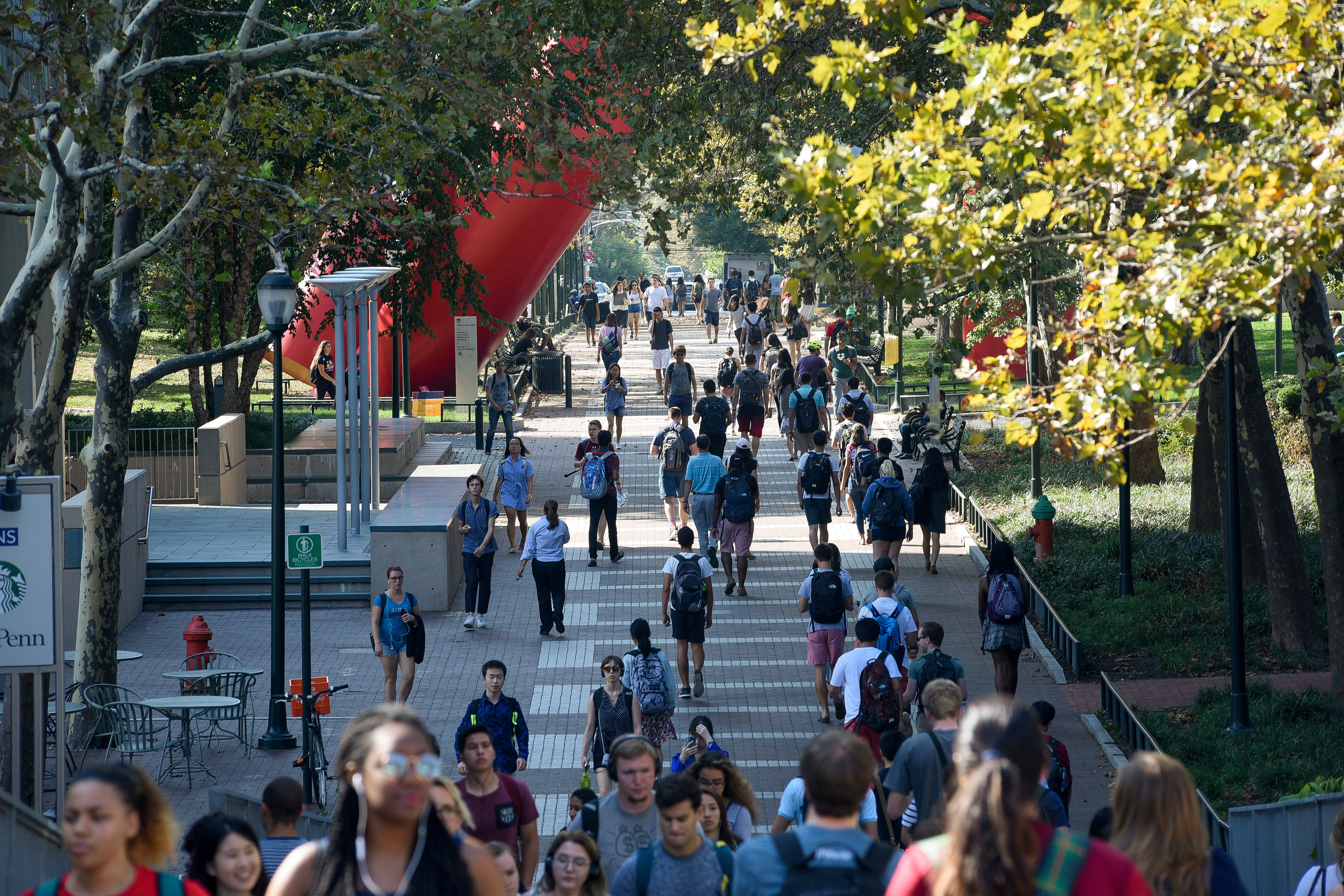 Students walk between classes on the Locust Walk on the campus of the University of Pennsylvania in Philadelphia, Pennsylvania, U.S., September 25, 2017. REUTERS/Charles Mostoller - RC1B82E07EF0