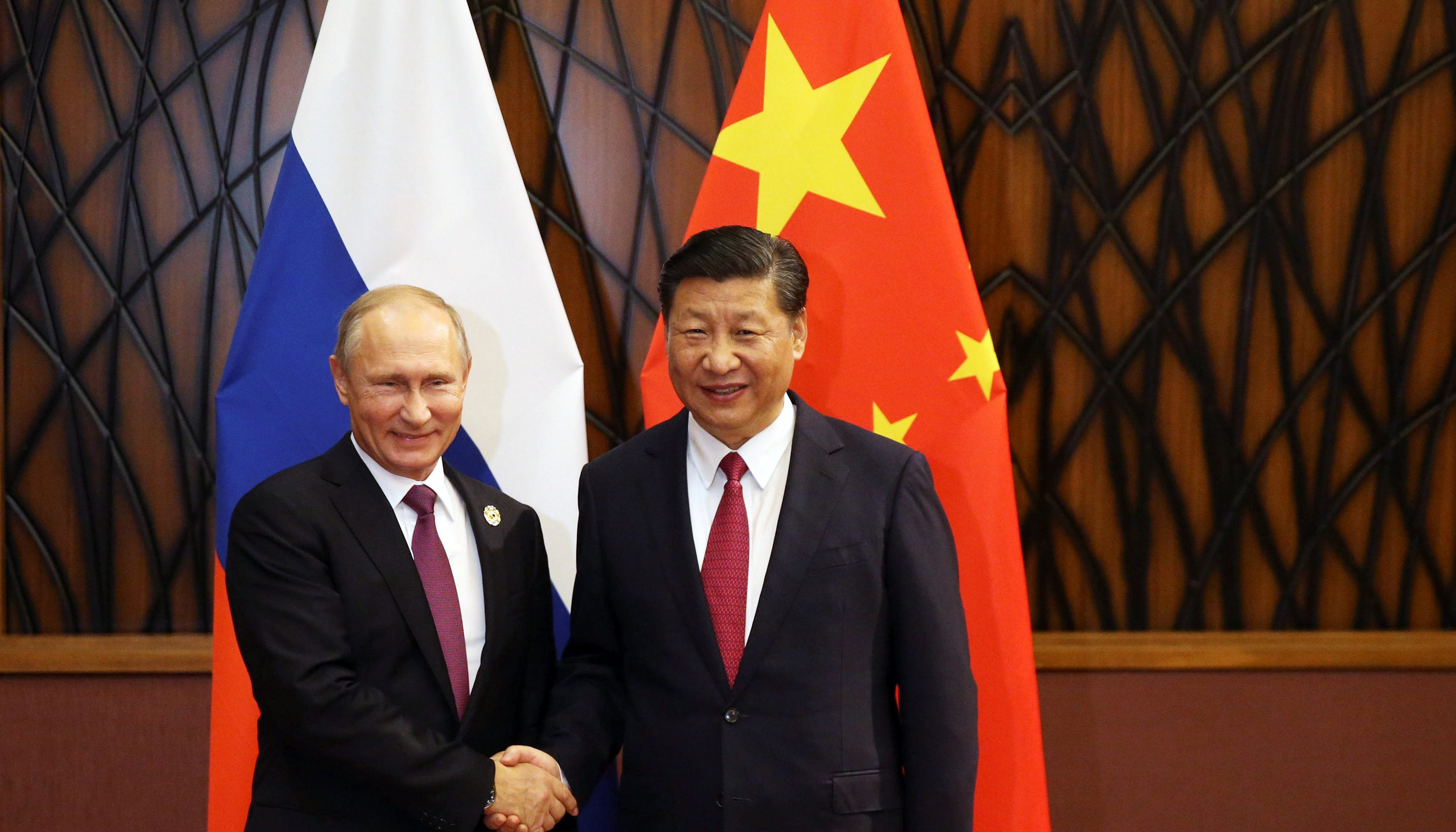 Russian President Vladimir Putin and Chinese President Xi Jinping shake hands during a meeting on the sidelines of the APEC summit in Danang, Vietnam November 10, 2017. Sputnik/Konstantin Zavrazhin/Kremlin via REUTERS ATTENTION EDITORS - THIS IMAGE WAS PROVIDED BY A THIRD PARTY. - RC1BB457E1C0