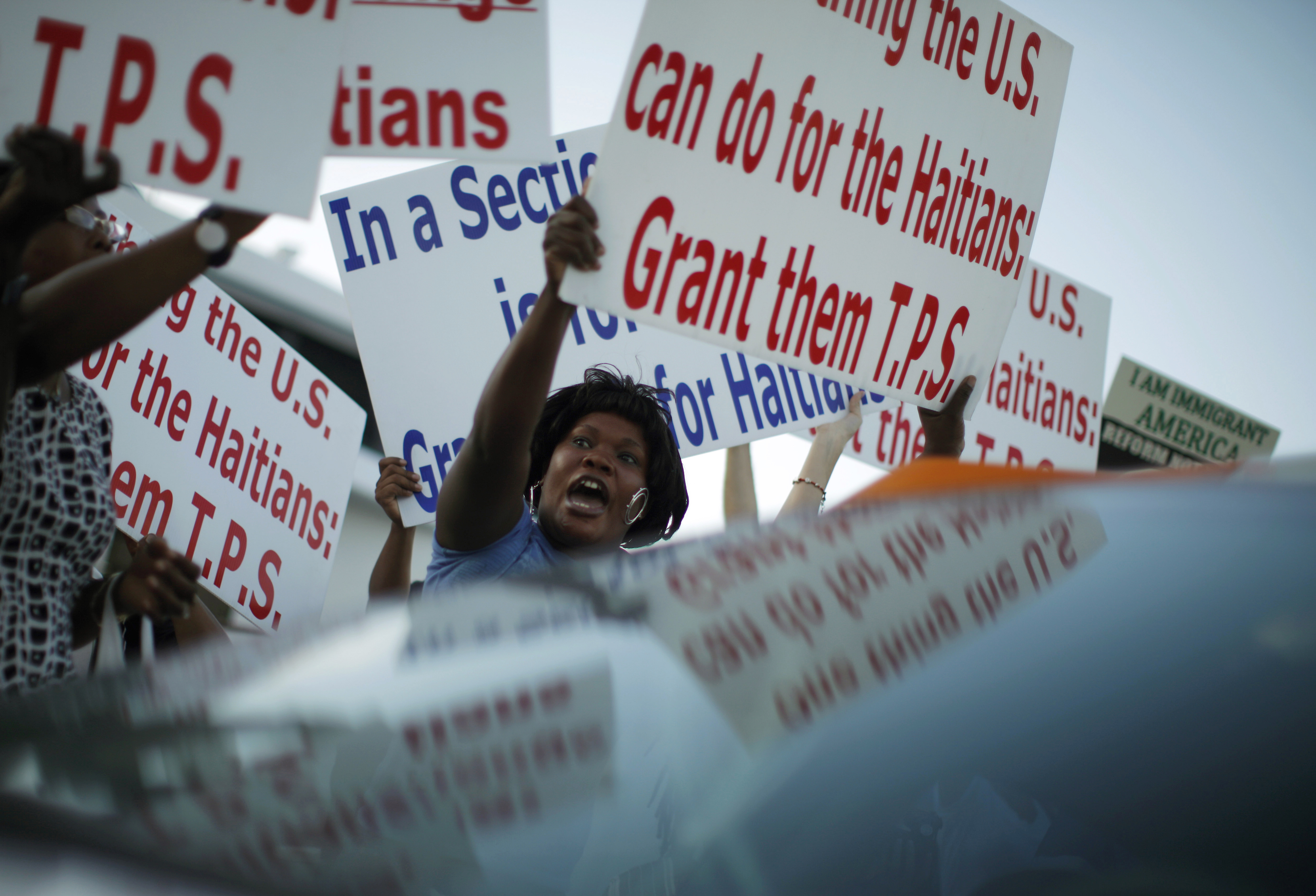Protesters hold up signs in favor of granting Haitian refugees TPS.