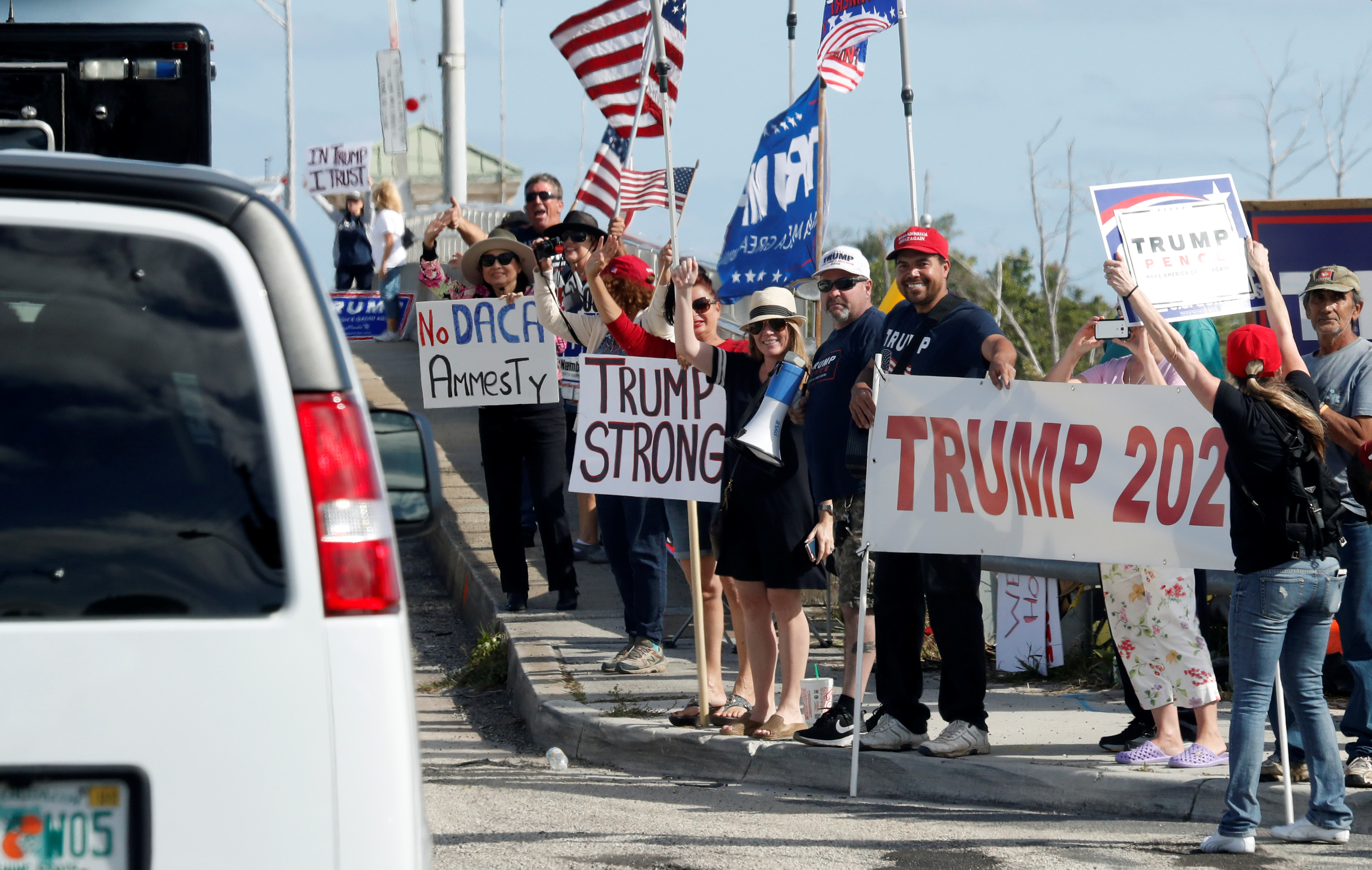 Supporters hold up signs as U.S. President Donald Trump's motorcade passes by in West Palm Beach, Florida, U.S., January 13, 2018. REUTERS/Kevin Lamarque