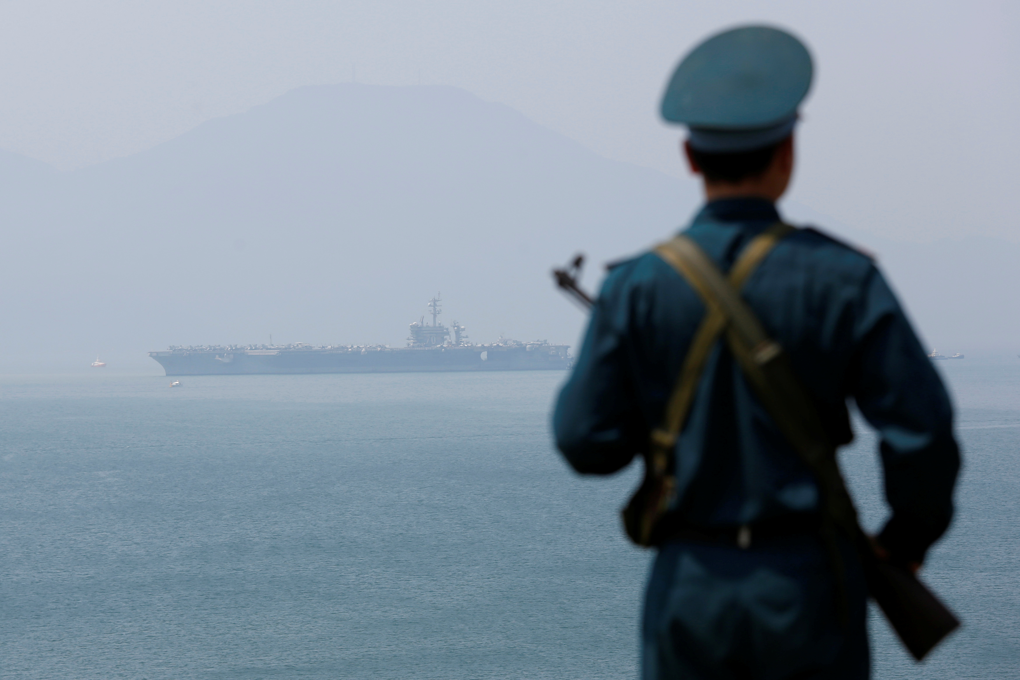 A Vietnamese soldier keeps watch in front of U.S. aircraft carrier USS Carl Vinson after its arrival at a port in Danang, Vietnam March 5, 2018. REUTERS/Kham - RC1CCE413490