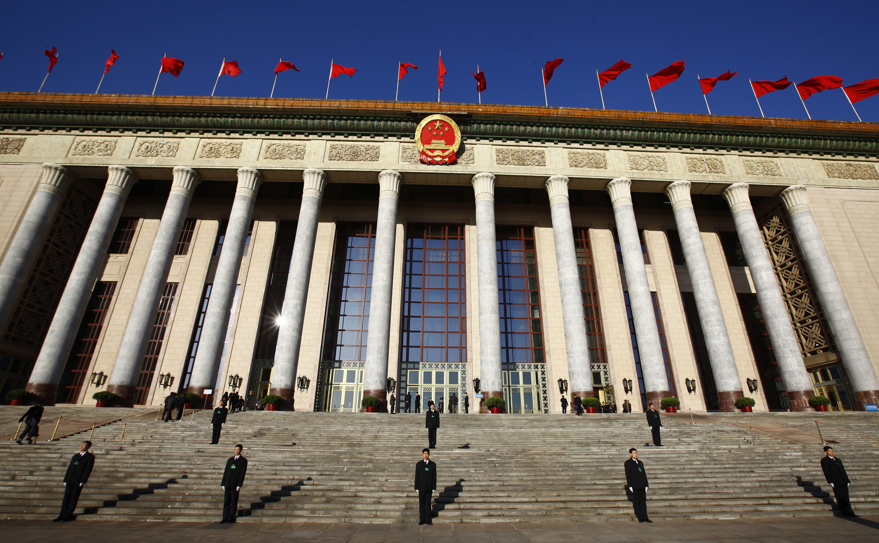 Security officers stand guard outside the Great Hall of the People during the third plenary session of the National People's Congress (NPC) in Beijing March 10, 2013.