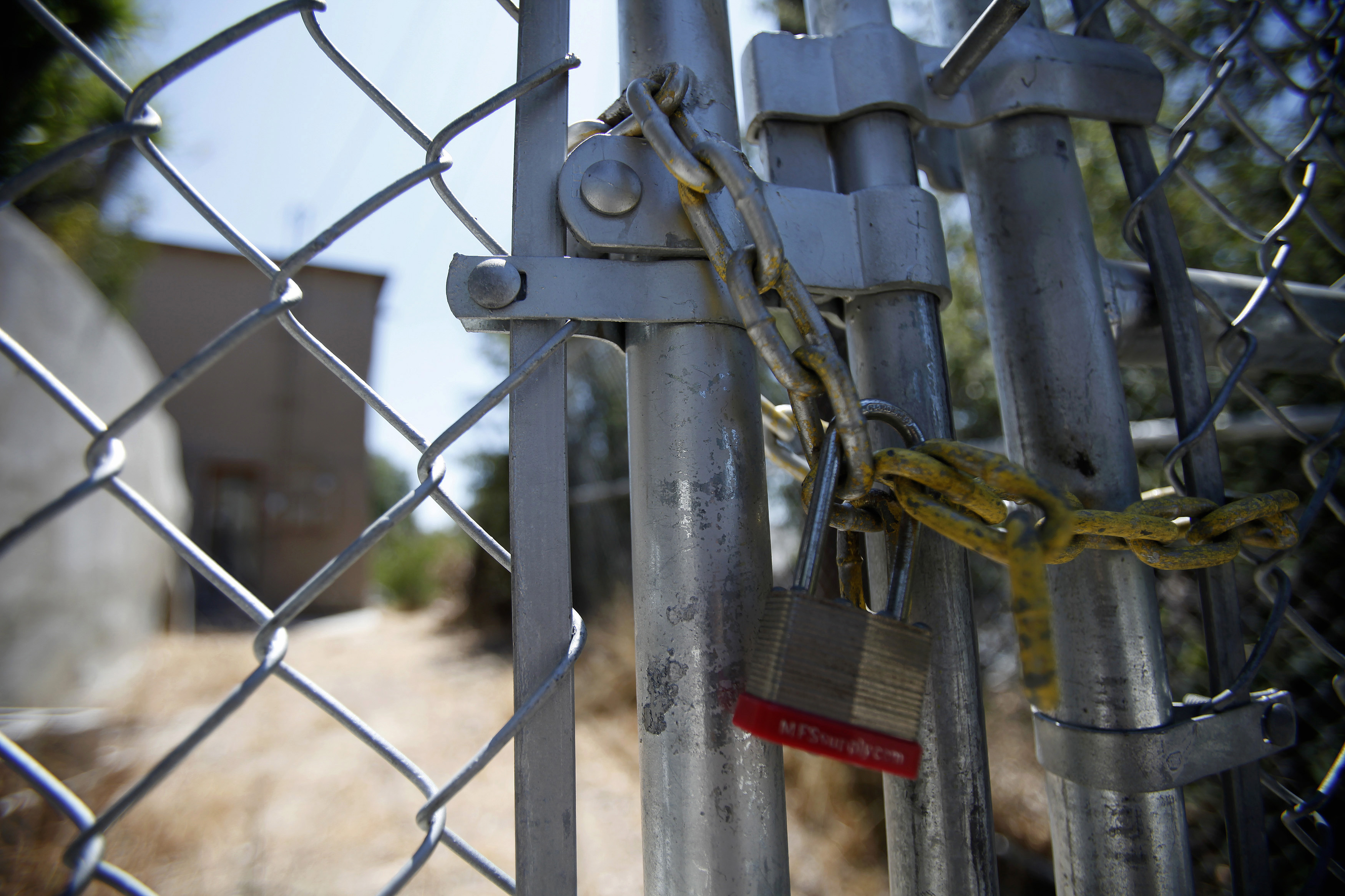 A lock secures a chain on the steel fence of a foreclosed home.