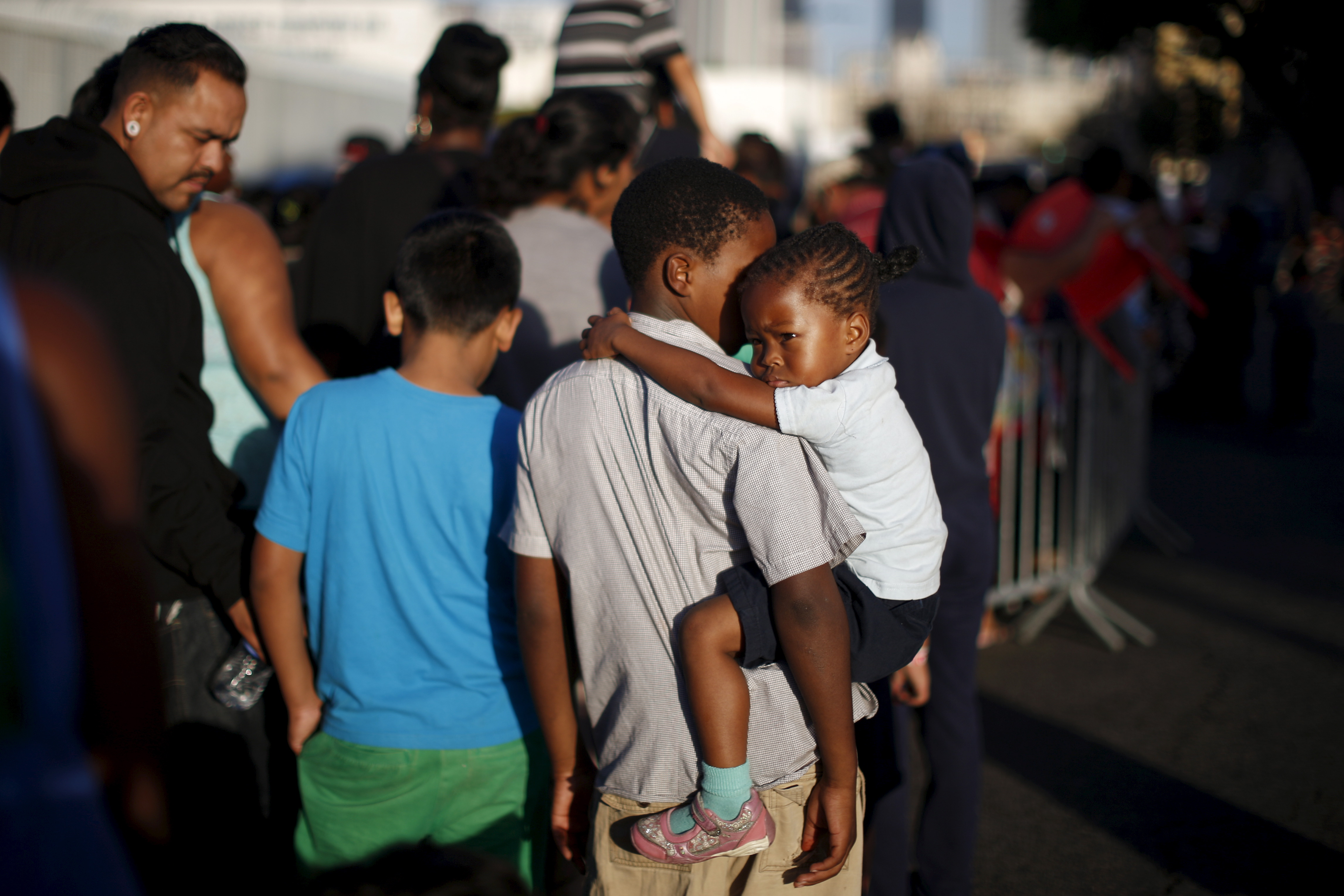People wait in line at the Fred Jordan Mission annual back to school giveaway of shoes, clothing and backpacks for more than 4,000 homeless and underprivileged children in Los Angeles, California, United States, October 1, 2015.