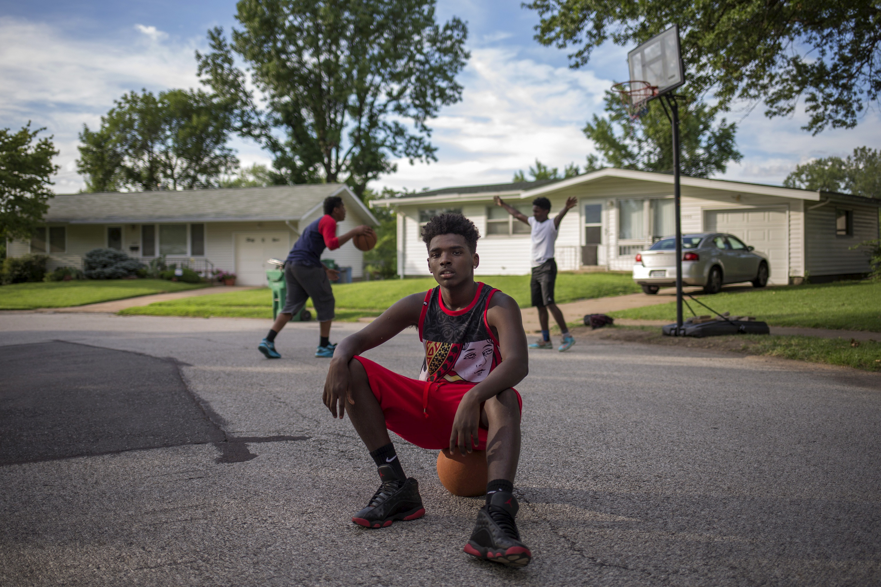 """Randy Johnson, 17, a high school student, poses for a portrait between games of basketball outside a friend's residence in Ferguson, Missouri July 21, 2015. When asked how Michael Brown's death affected him, Johnson said, """"I don't trust the law anymore. I could be next."""" When asked what changes he has seen in his community over the past year, Johnson said, """"The police don't come around no more. They don't want an incident like that."""" On August 9, 2014 a white police officer shot unarmed black teenager Michael Brown dead in the St. Louis suburb of Ferguson, Missouri."""