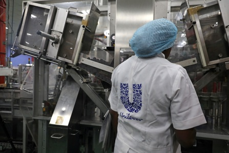 A woman stands behind a machine that is part of a toothpaste manufacturing line at the Unilever factory in Lagos, Nigeria January 18, 2018. Picture taken January 18, 2018. REUTERS/Afolabi Sotunde - RC18940C2B90