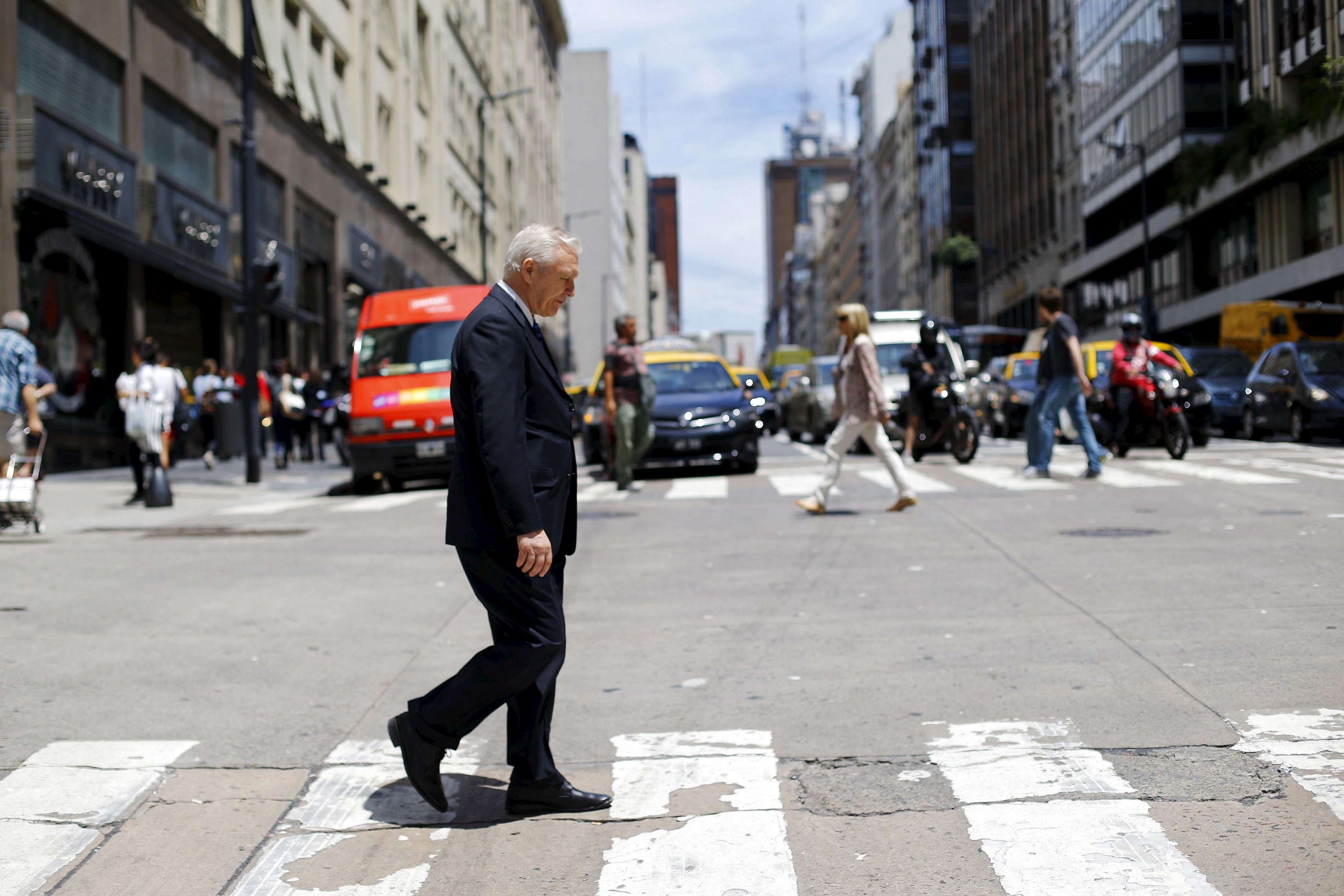 """A man crosses """"Corrientes"""" avenue in a financial area in downtown Buenos Aires, Argentina, November 23, 2015. Argentine bond prices were giving back some earlier gains on Monday as investors took profits following a widely expected victory for market favorite Mauricio Macri in the presidential elections over the weekend. REUTERS/Ivan Alvarado - GF20000071141"""