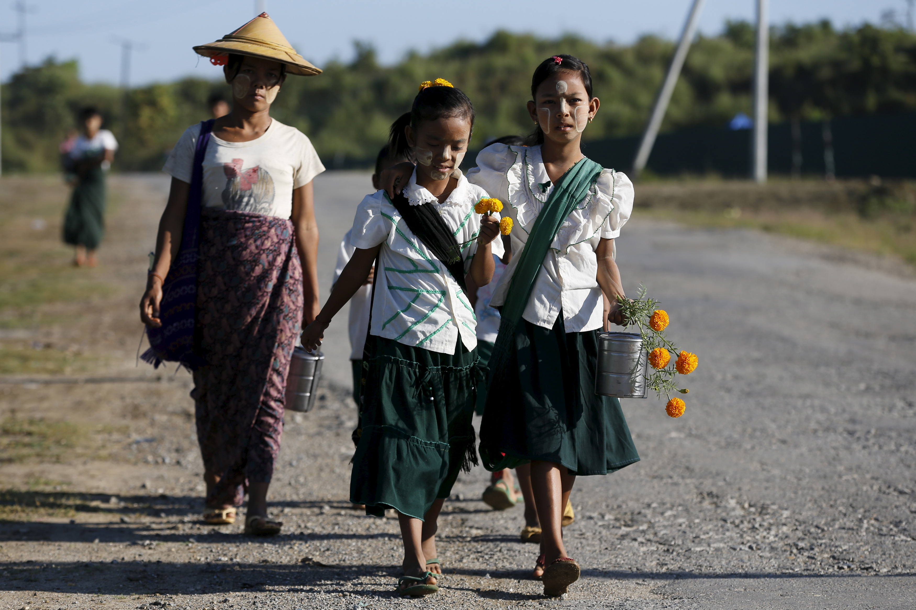 Girls walk to school at the outskirts of Yangon November 4, 2015. Myanmar on November 8 is holding its first free and fair election in 25 years in which democracy icon Aung San Suu Kyi is pitted against the ruling party comprised of former members of a military junta. REUTERS/Jorge Silva - GF20000044866