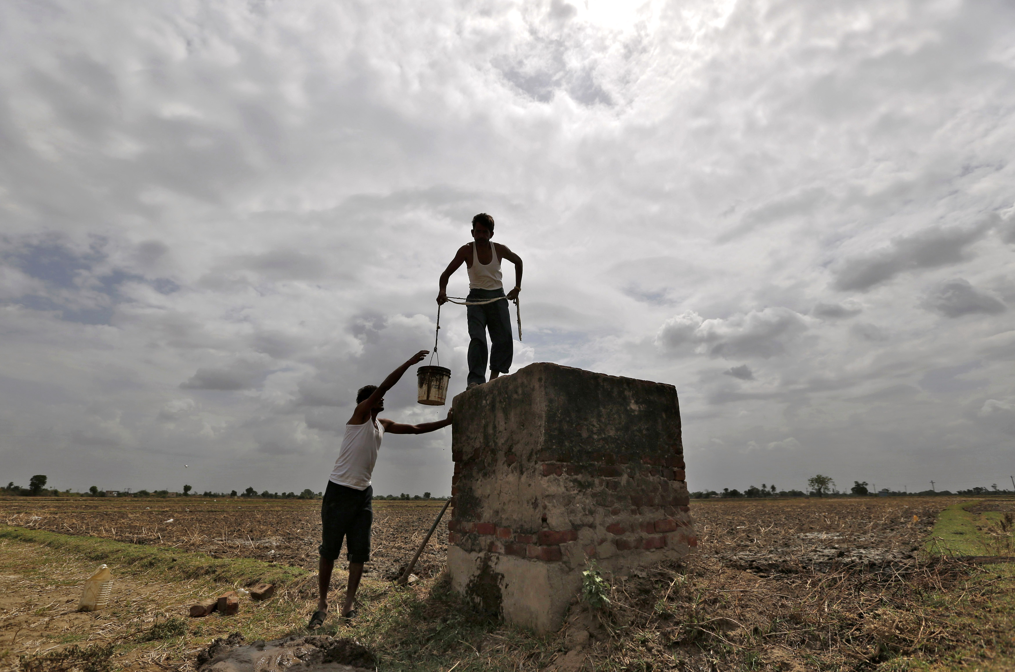 """Farmers are pictured under monsoon clouds as they clean a canal water tank at Shantipura village in the western Indian state of Gujarat July 2, 2014. Rains are forecast to gain momentum over most of the country early this month, but the farm minister said on Tuesday that a """"drought-like situation might prevail in some pockets"""" of western India. REUTERS/Amit Dave (INDIA - Tags: AGRICULTURE ENVIRONMENT SOCIETY) - GM1EA721IJD01"""