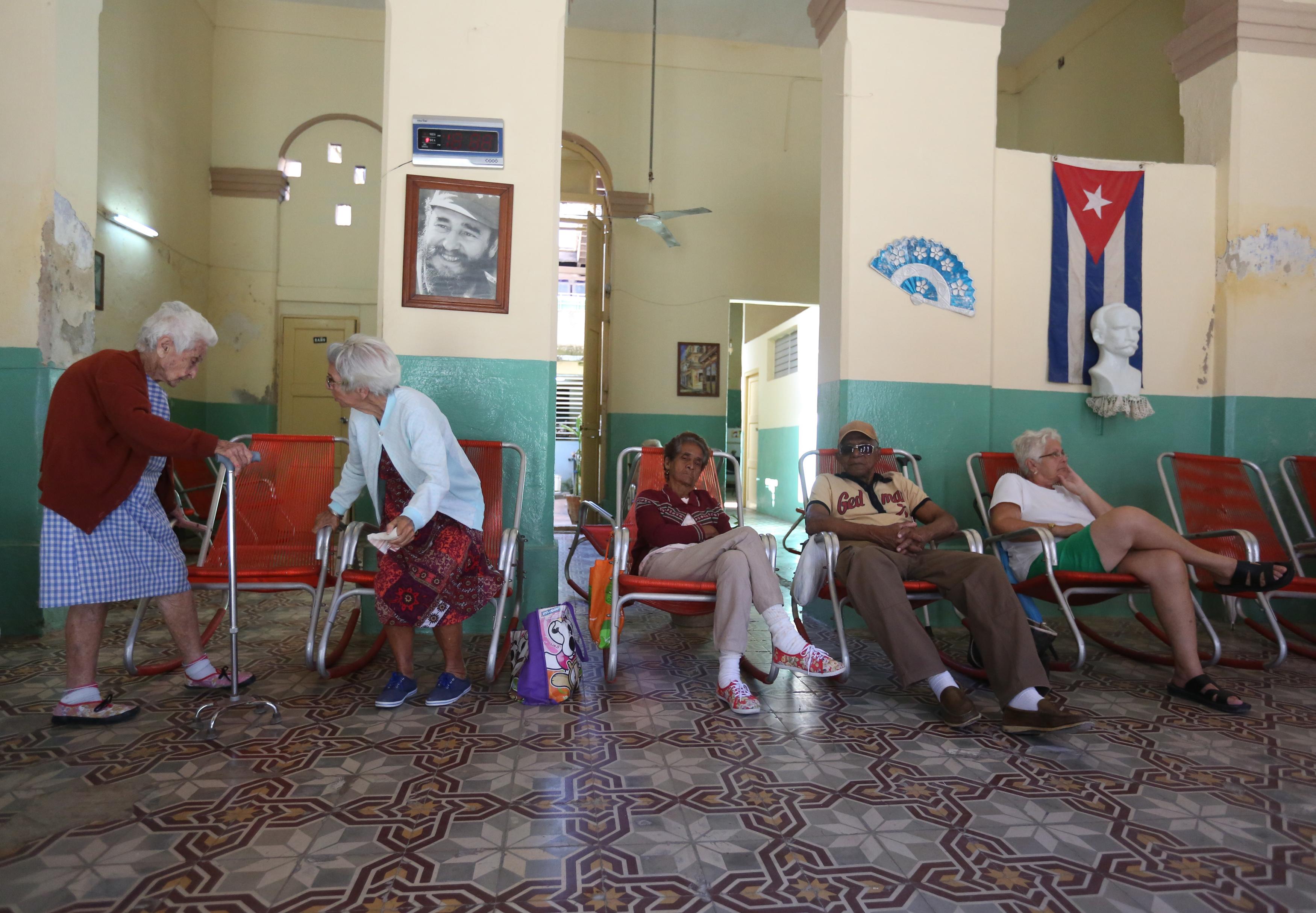 Elderly Cubans sit by an image of Cuba's late President Fidel Castro (L) at a retirement home in the Regla neighborhood in Havana, Cuba, November 29, 2016. REUTERS/Edgard Garrido - HT1ECBT1DDJBU