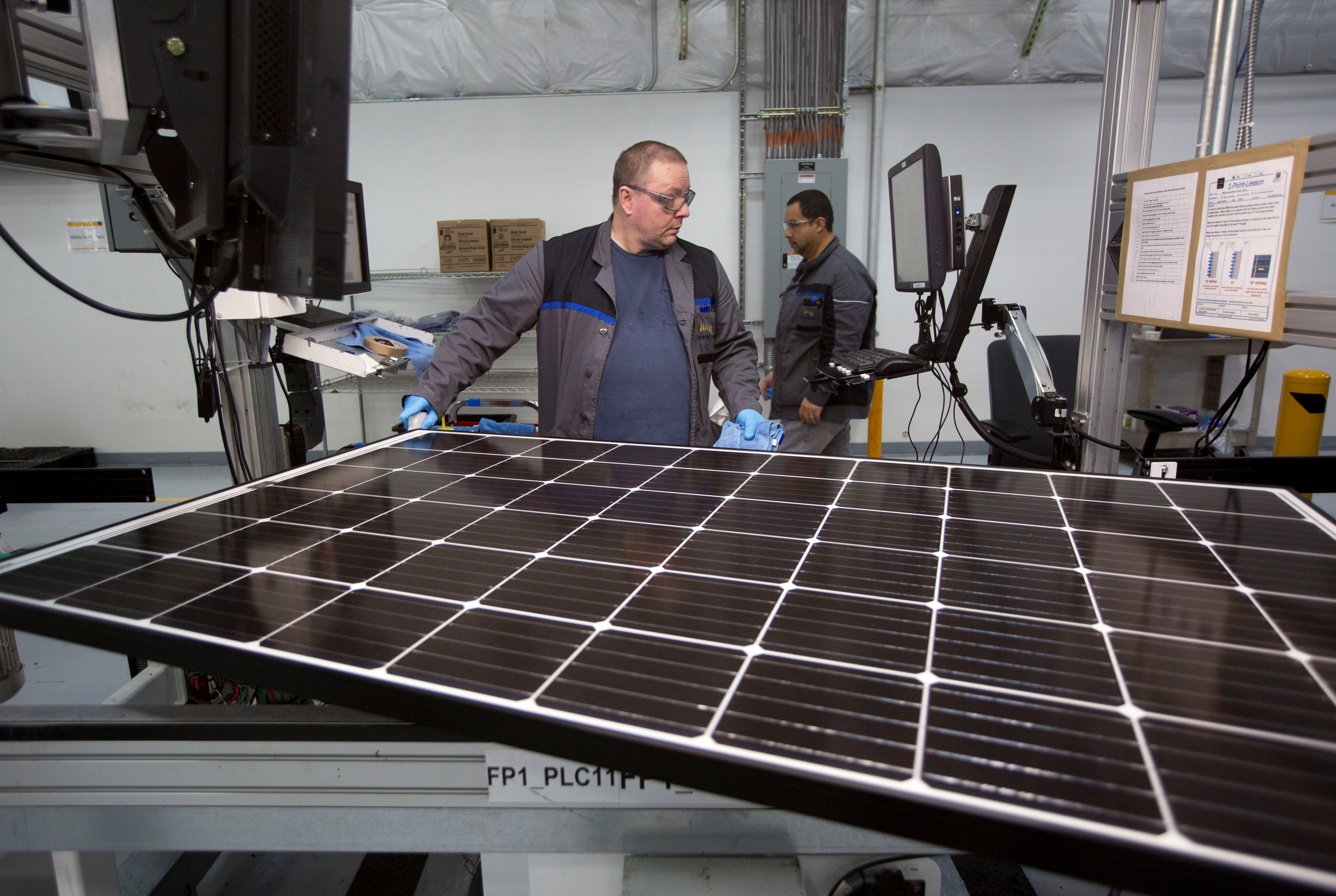 Production operator John White checks a panel at the SolarWorld solar panel factory in Hillsboro, Oregon, U.S., January 15, 2018. Picture taken January 15, 2018. REUTERS/Natalie Behring - RC1A2904F740