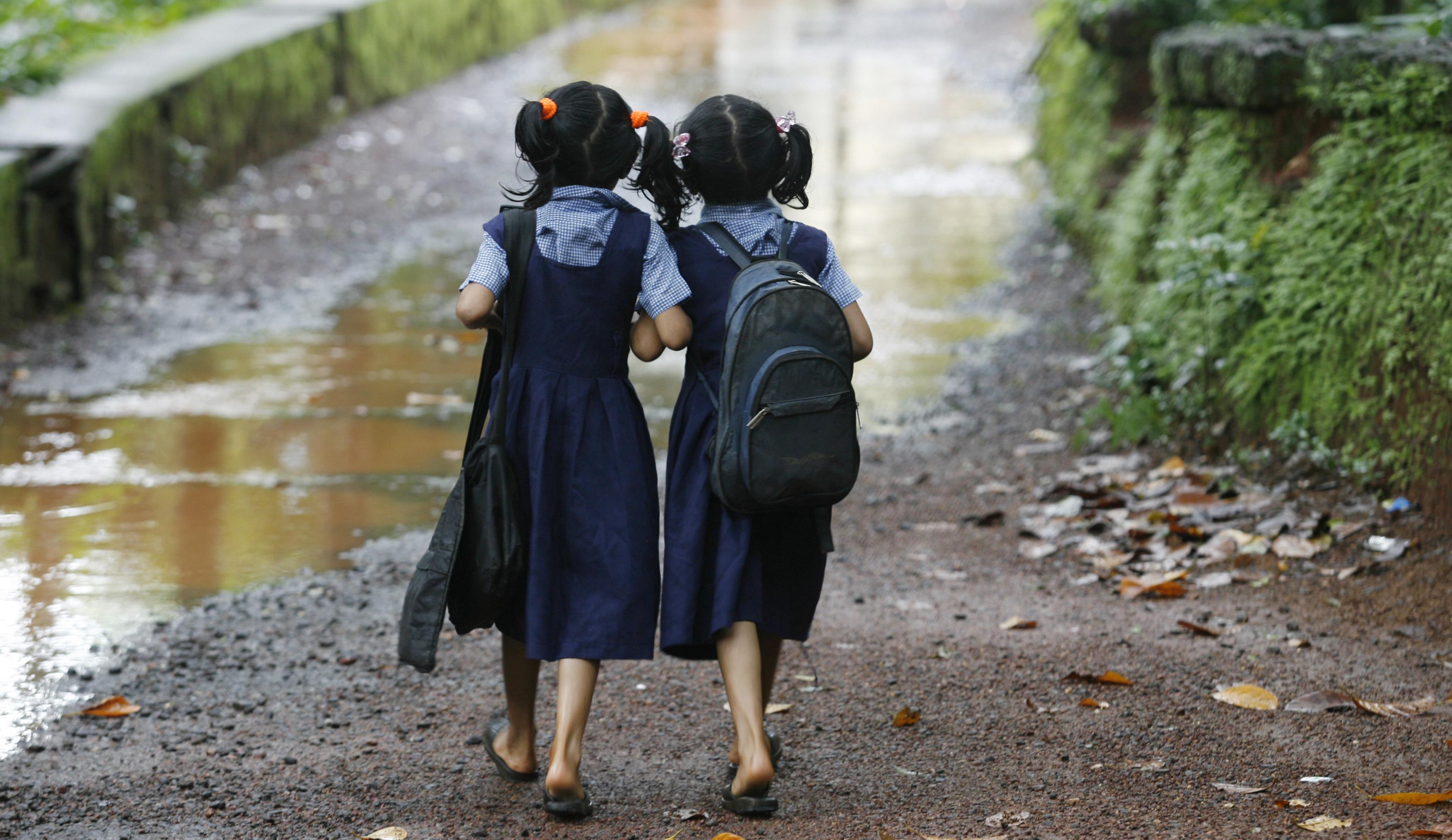 Twin girls walk to their school in Kodinji village in the southern Indian city of Kerala