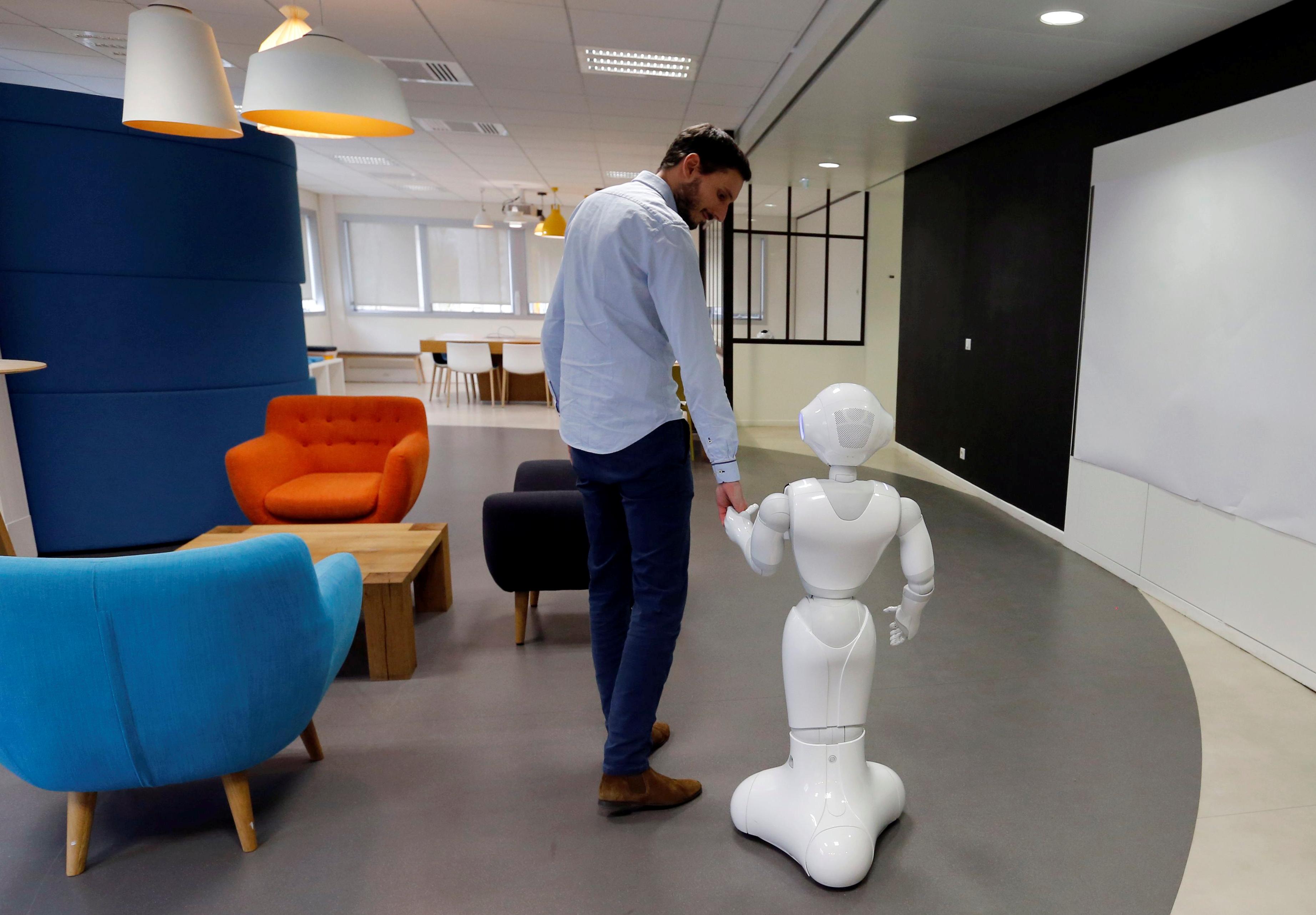 An employee of SoftBank Robotics walks with the Robot Assistant Pepper in Paris, France, March 9, 2018. Picture taken March 9, 2018. REUTERS/Regis Duvignau - RC1D026FA390