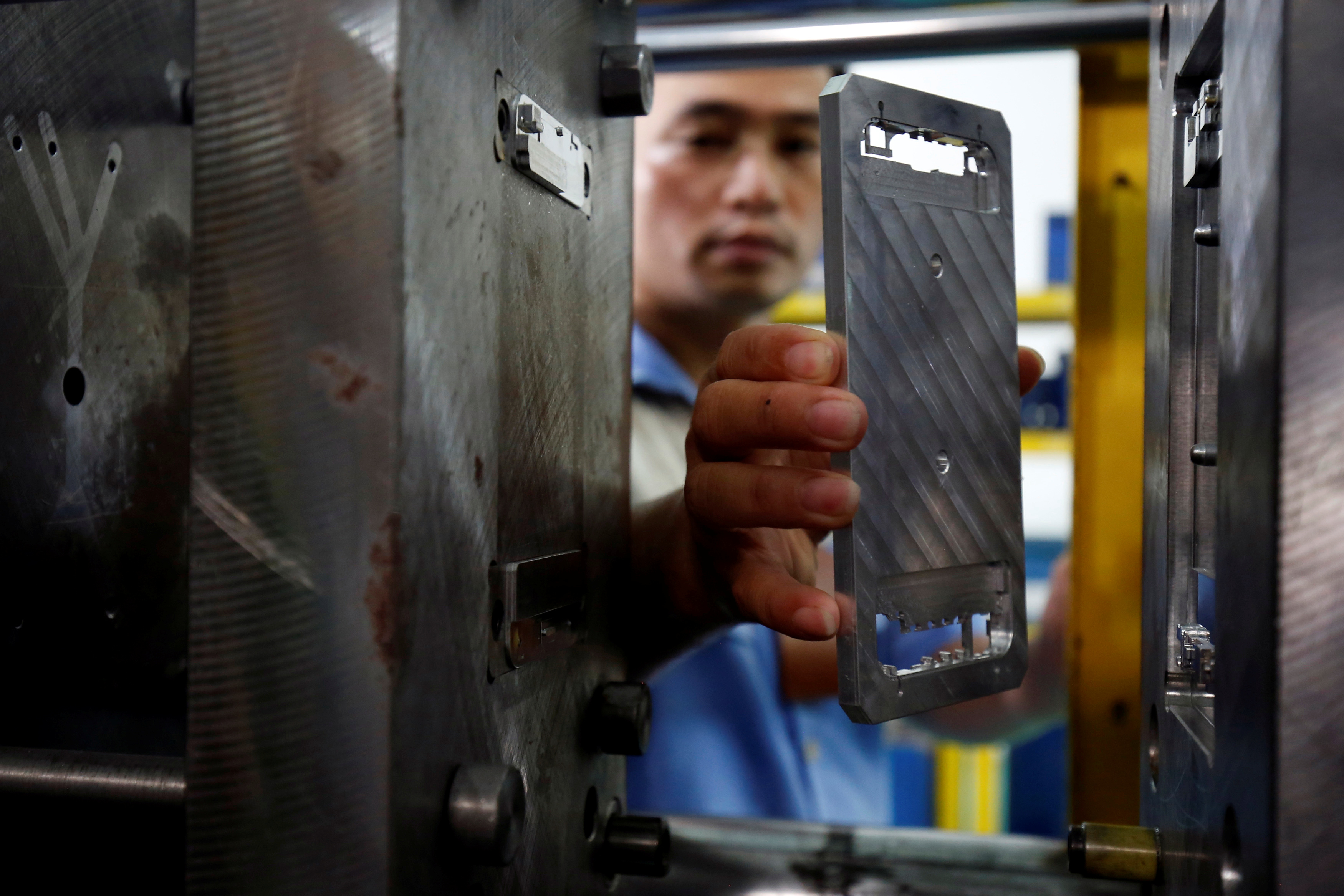 A worker holds a metal frame at an assembly plant that produces the Vietnamese smartphone BPhone, at BKAV factory, in Hanoi, Vietnam July 5, 2017. REUTERS/Kham - RC1EB392CA80