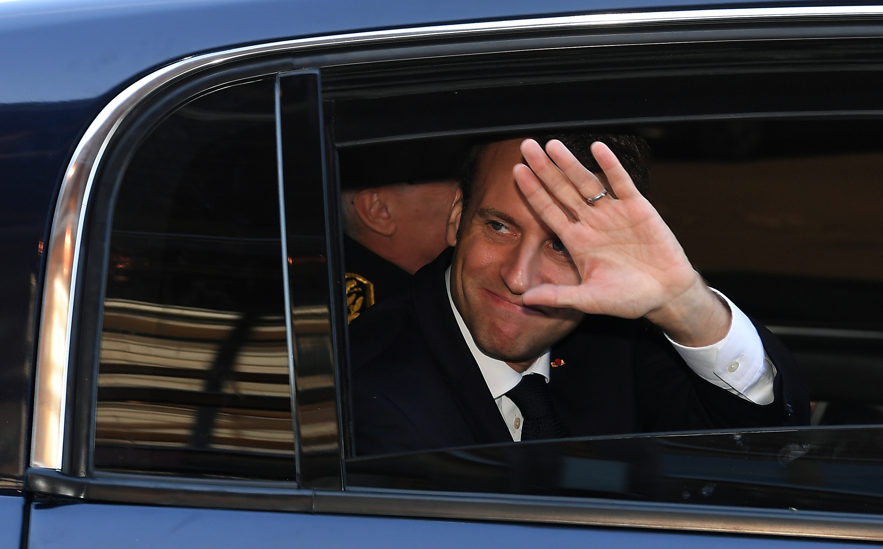 French President Emmanuel Macron waves from his car as he leaves after a visit about local and organic food supply in school canteens, at the secondary school Guy Dolmaire in Mirecourt, France, April 19, 2018. Patrick Hertzog/Pool via Reuters - RC148066A640