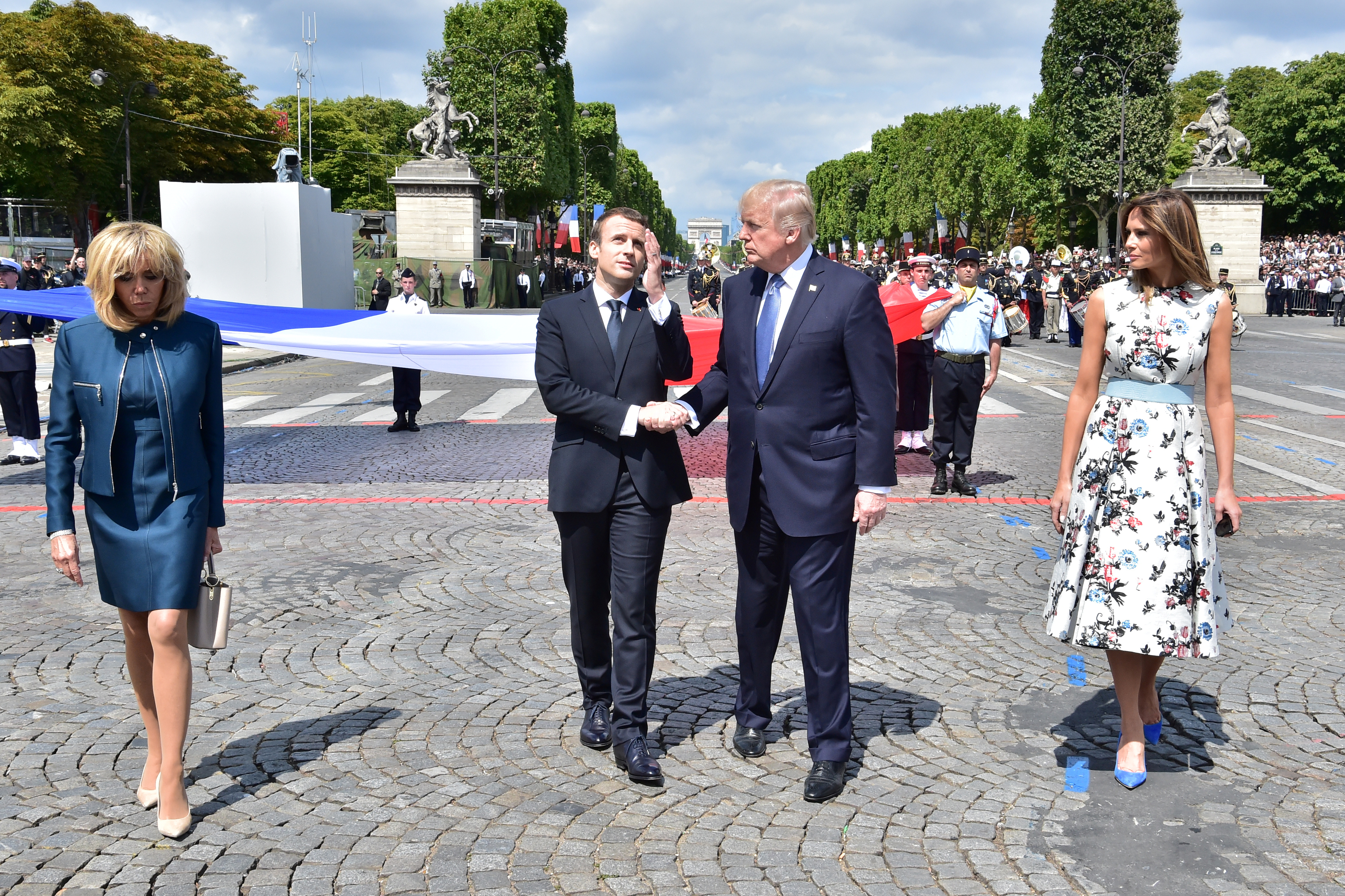 French President Emmanuel Macron (C-L) shakes hands with U.S. President Donald Trump, next to Macron's wife Brigitte Macron (L) and U.S. First Lady Melania Trump during the traditional Bastille Day military parade on the Champs-Elysees avenue in Paris, France, July 14, 2017. REUTERS/Christophe Archambault/Pool - RC127EEC3070