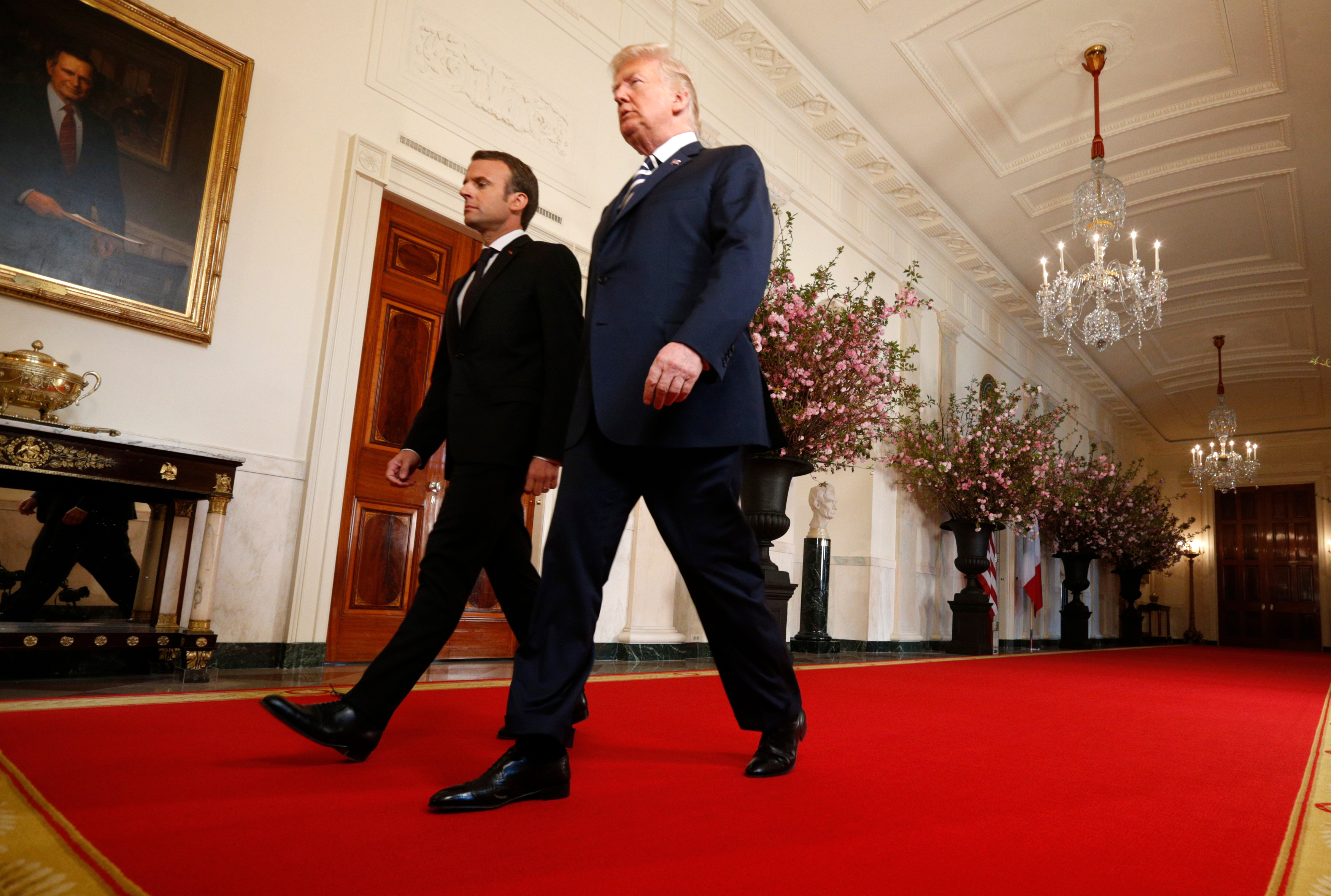 U.S. President Donald Trump (R) and French President Emmanuel Macron walk through the cross hall of the White House as they arrive for their joint news conference in Washington, U.S., April 24, 2018. REUTERS/Kevin Lamarque - HP1EE4O1EPJAX