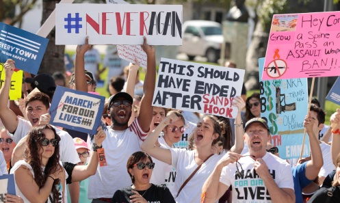 """Students hold signs while rallying in the street during the """"March for Our Lives"""" demanding stricter gun control laws at the Miami Beach Senior High School, in Miami, Florida, U.S., March 24, 2018. REUTERS/Javier Galeano - RC1C60279010"""