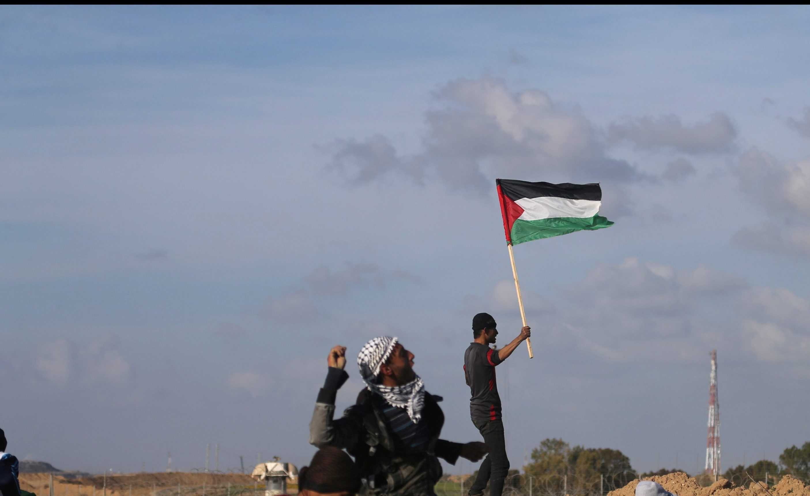 A demonstrator waves a Palestinian flag during clashes with Israeli troops at a protest against U.S. President Donald Trump's decision on Jerusalem, near the border with Israel in the southern Gaza Strip March 16, 2018. REUTERS/Ibraheem Abu Mustafa - RC1D250522B0