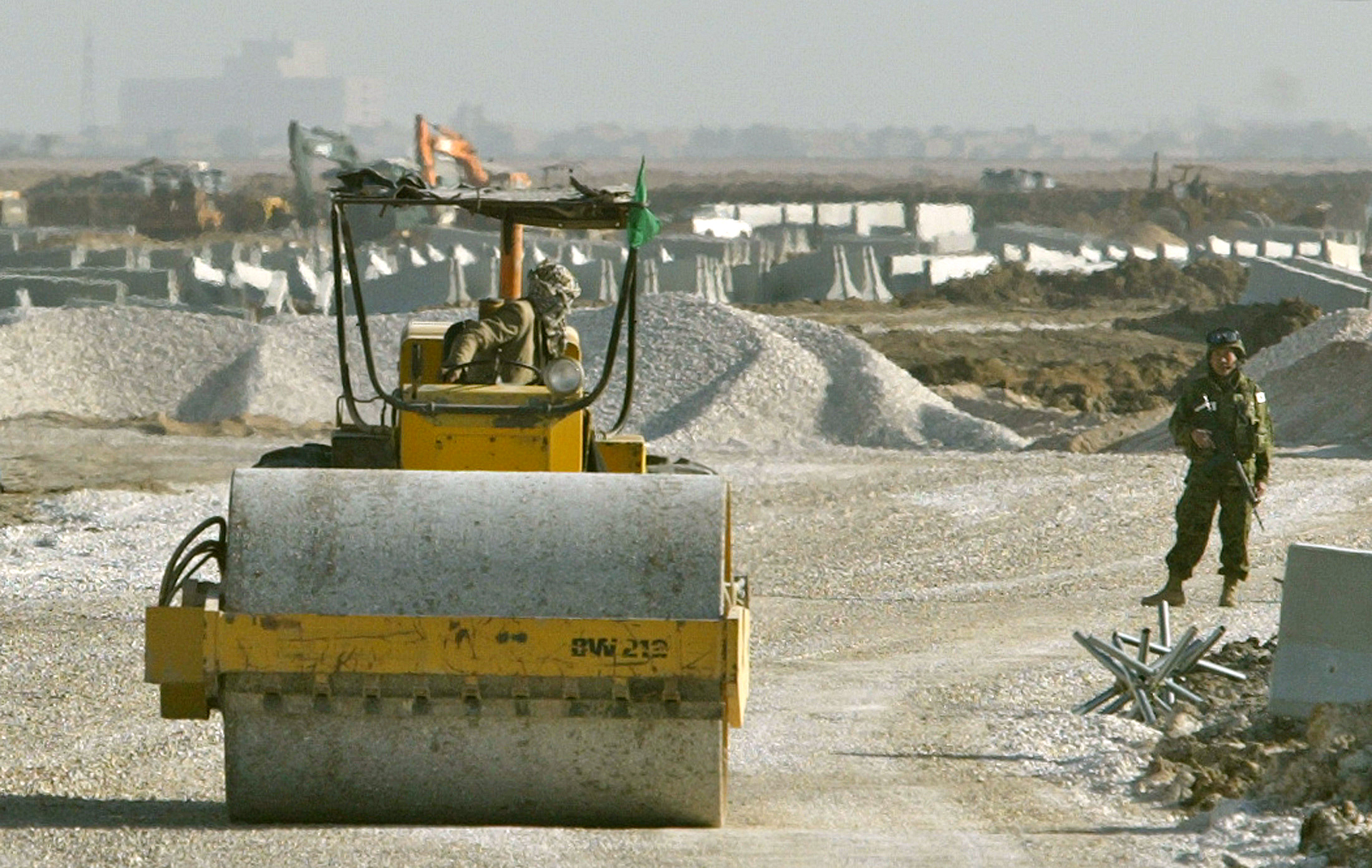 A soldier of the Japanese advanced team watches as an Iraqi construction worker prepares a road for their base outside the town of Samawa, some 300kms south of the Iraqi capital Baghdad February 21, 2004. Japan kept security tight across the country on Saturday as its largest contingent of troops to date prepared to leave on a controversial mission to Iraq. REUTERS/Peter Andrews  PA - RP4DRIASPQAA