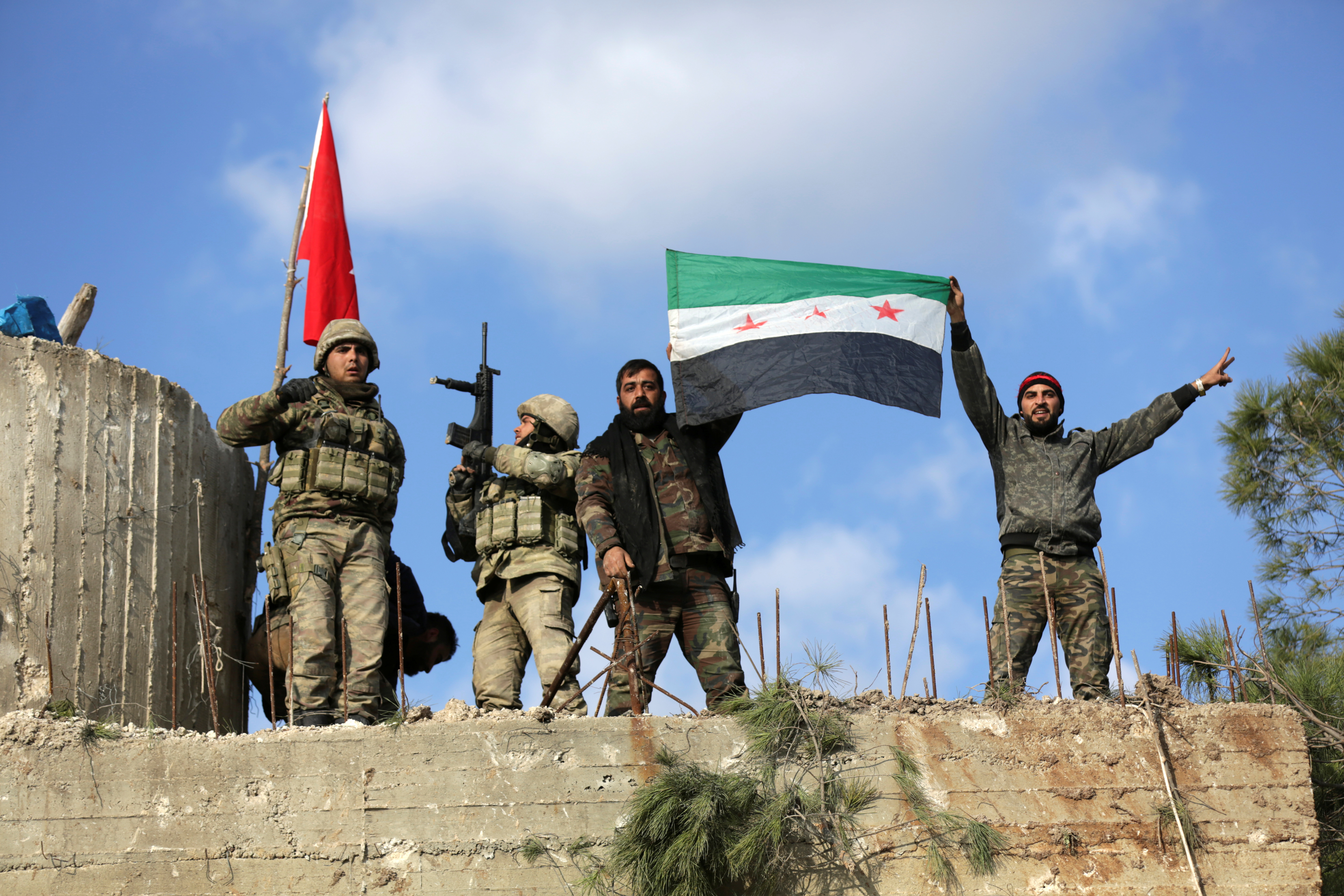 Turkish forces and Free Syrian Army members hold flags on Mount Barsaya, northeast of Afrin, Syria January 28, 2018. REUTERS/ Khalil Ashawi